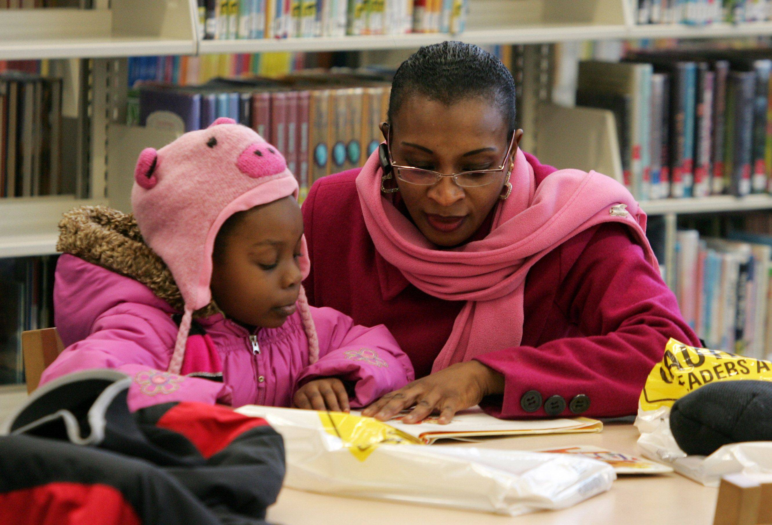 Tayseer Ibrahim, of Gurnee, reads to her 5-year-old daughter, Syriana Ugwu, in the juvenile section during the grand reopening celebration Sunday at the Warren-Newport Public Library in Gurnee.