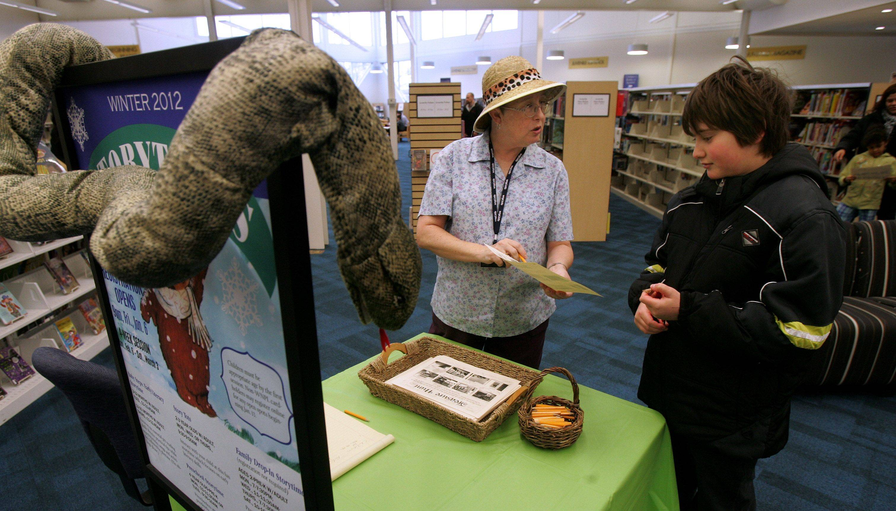 Volunteer Debbie Lessenberry explains the Treasure Hunt contest to Elias Driscoll, 10, during Sunday's grand reopening celebration at the Warren-Newport Public Library in Gurnee.