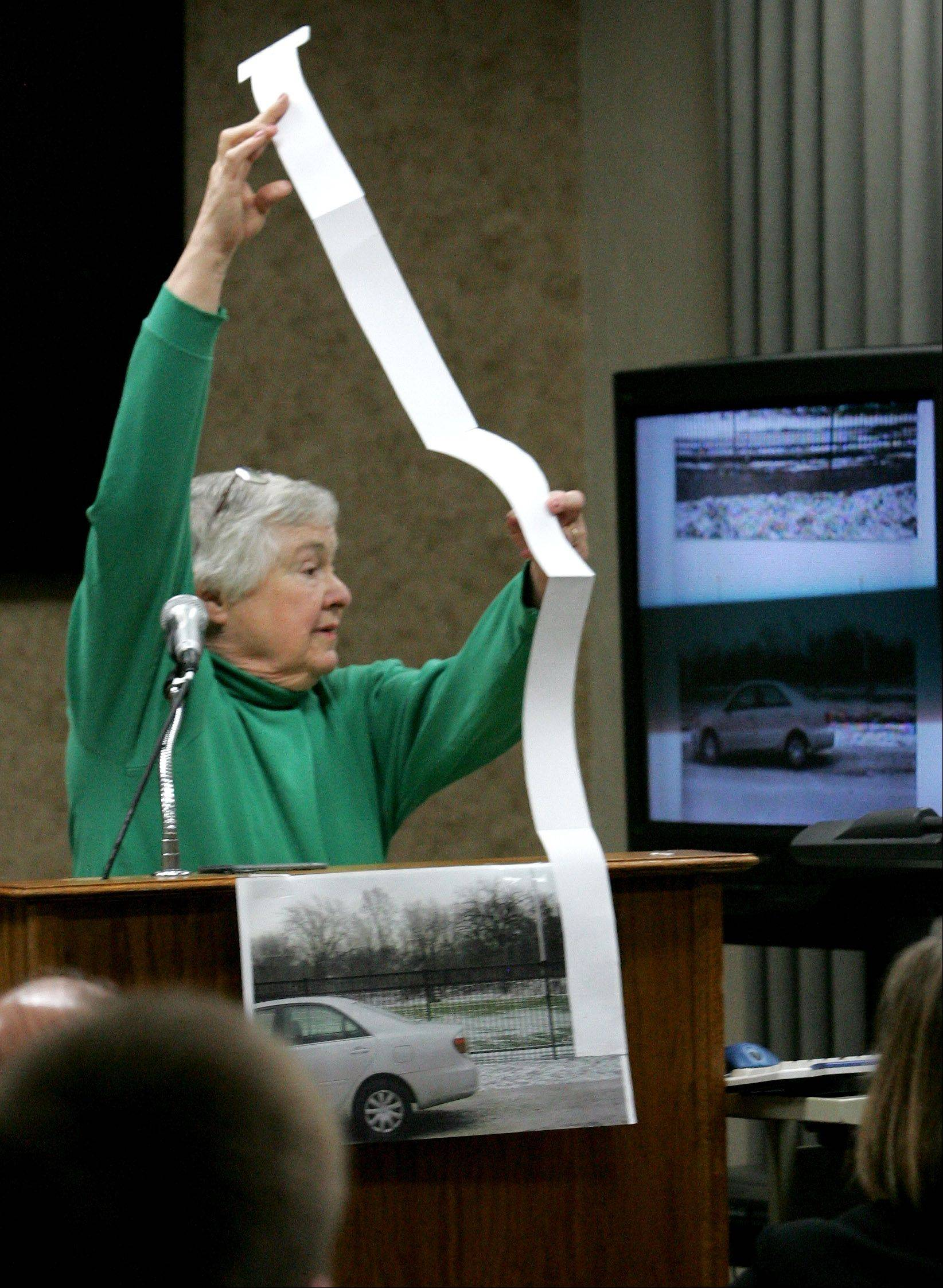 Glen Ellyn resident Rinda Allison demonstrates how tall the proposed lights at Memorial Field will be during public comment at a village board meeting Monday.