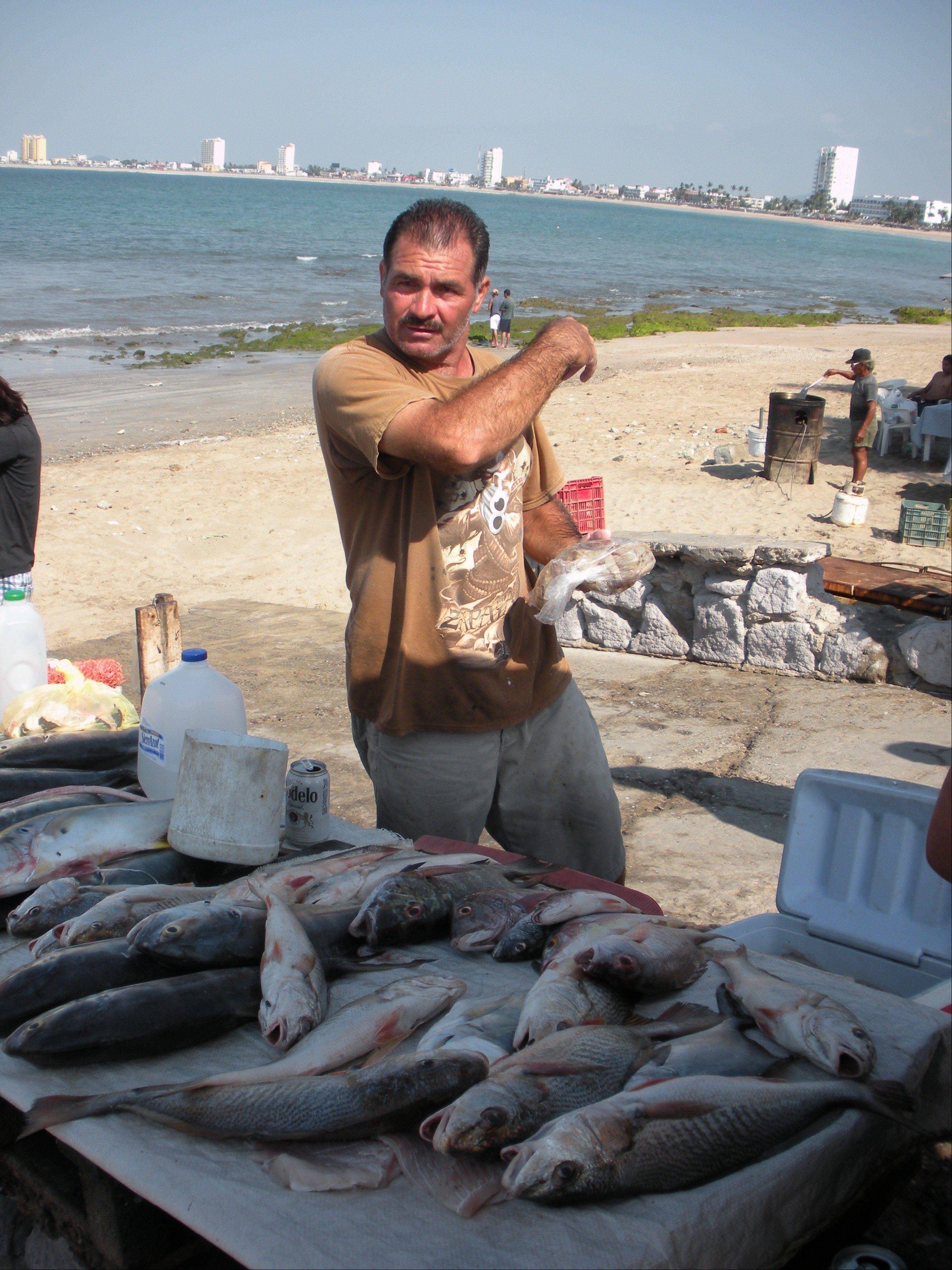A fisherman displays his morning bounty. Some of Mazatlan's shrimp and other fresh seafood finds its way to Chicago restaurants.