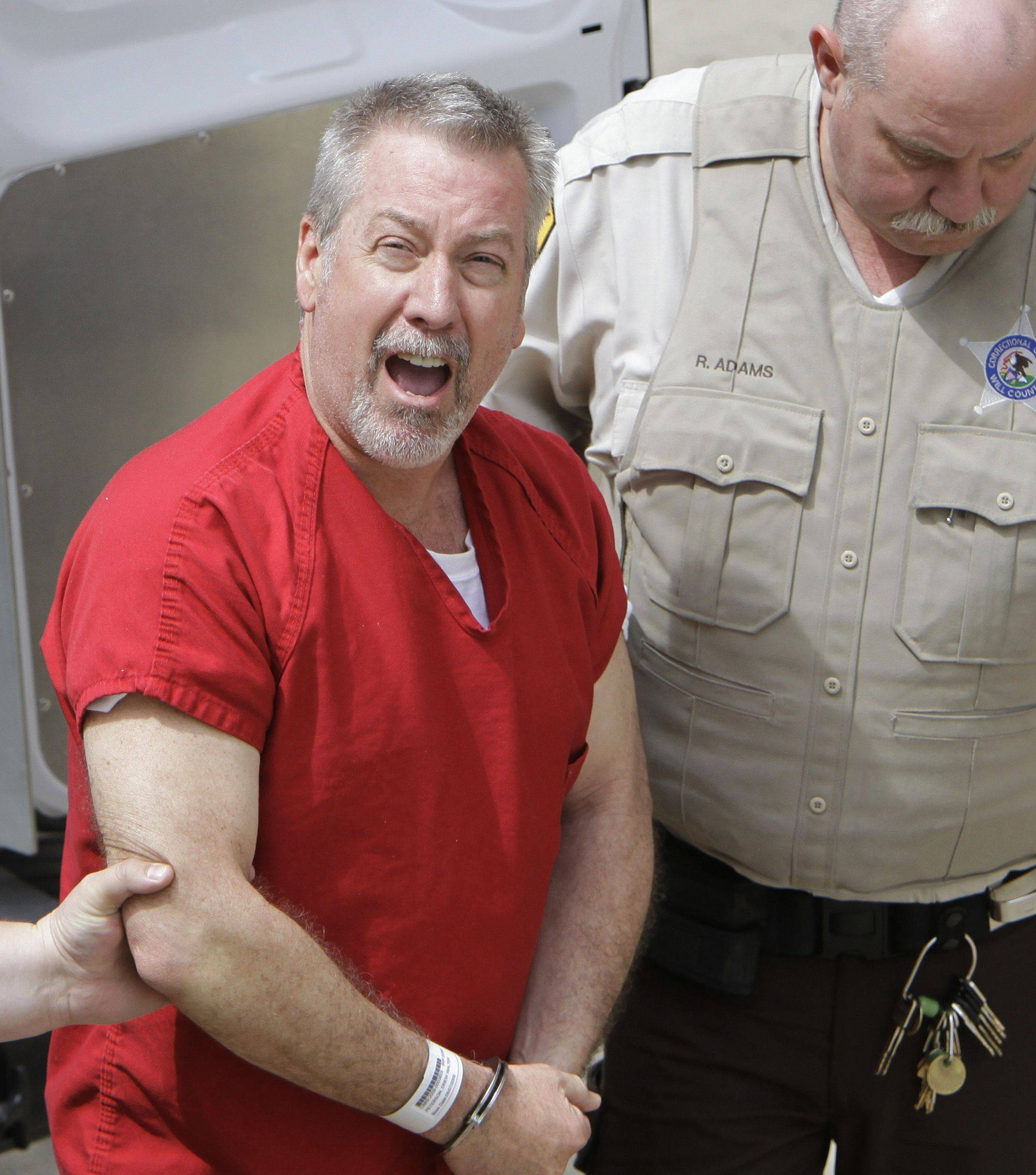 Former Bolingbrook police sergeant Drew Peterson yells to reporters as he arrives at the Will County Courthouse in Joliet. New Illinois Supreme Court rules could allow cameras in the courtroom for his trial proceedings.