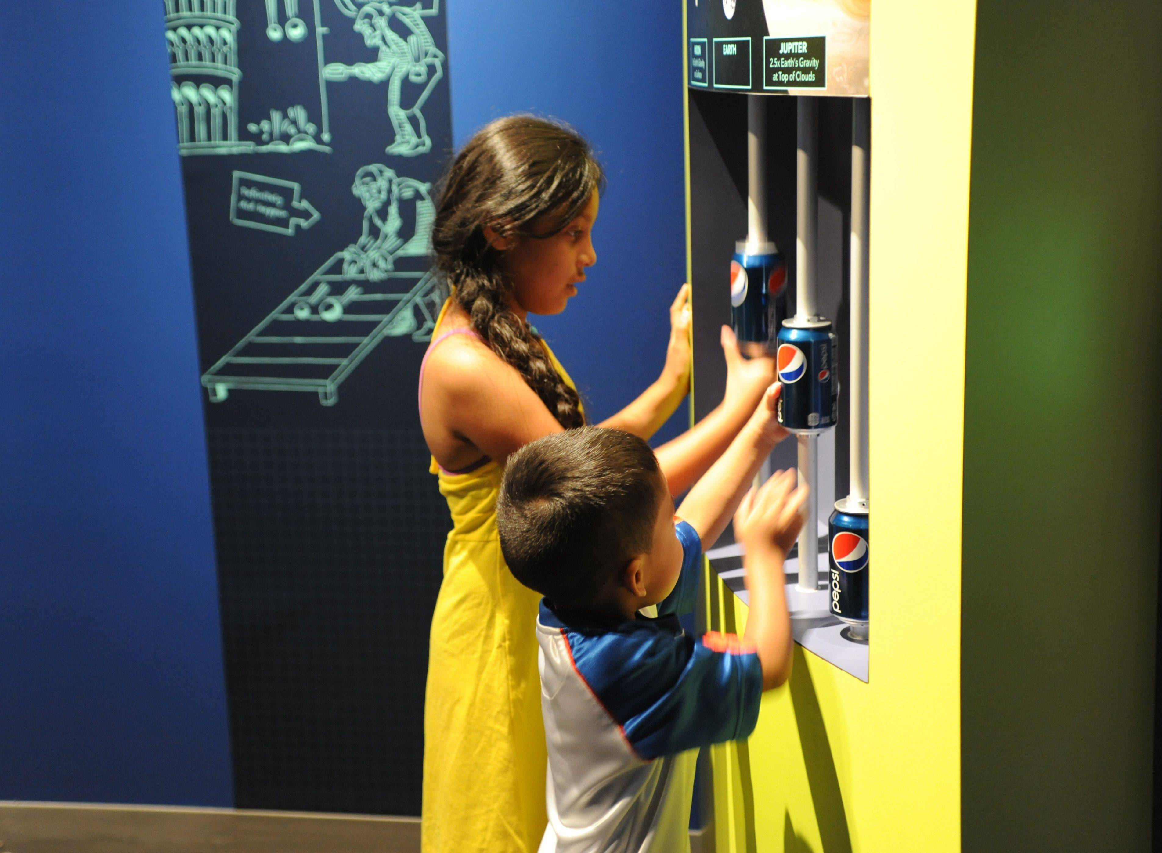 Young visitors experiment with the effects of gravity on the moon, Earth and Jupiter in a hands-on interactive in the Gravity exhibition at the Adler Planetarium in Chicago.