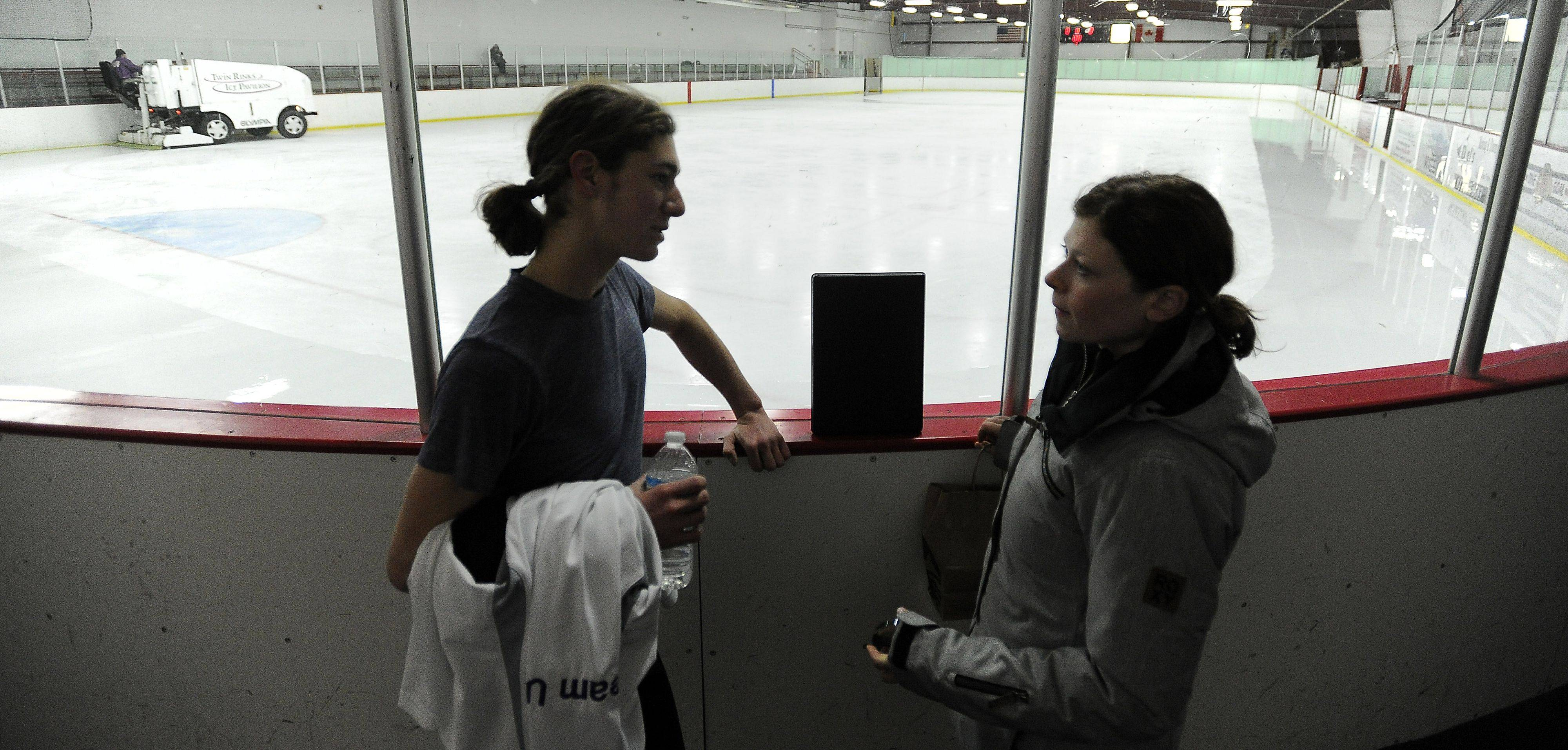Jason Brown talks with coach Kori Ade before he heads back onto the ice at Twin Rinks Arena in Buffalo Grove.