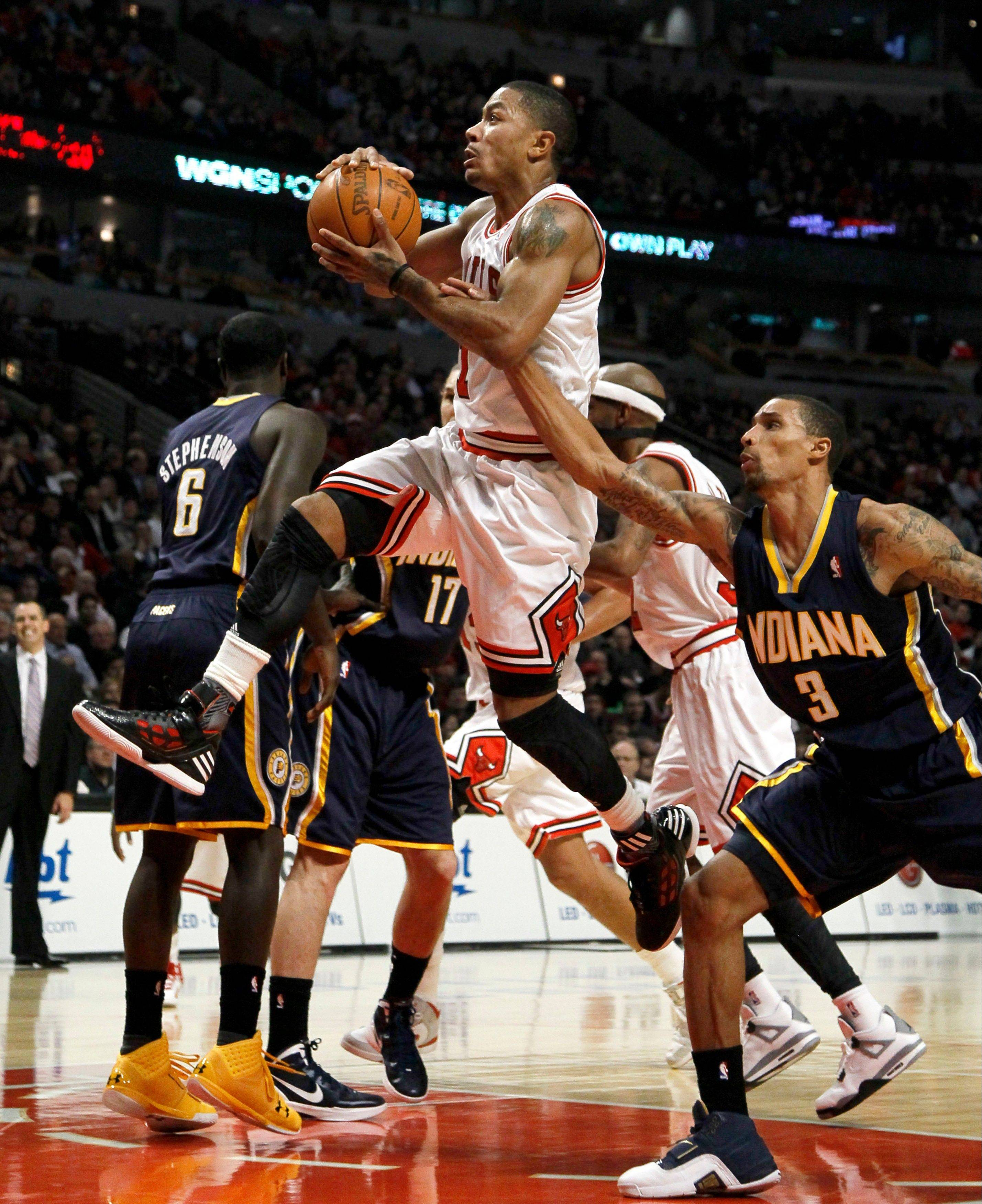 The Bulls' Derrick Rose drives and scores past Indiana Pacers shooting guard George Hill, right, during the first half Wednesday at the United Center.