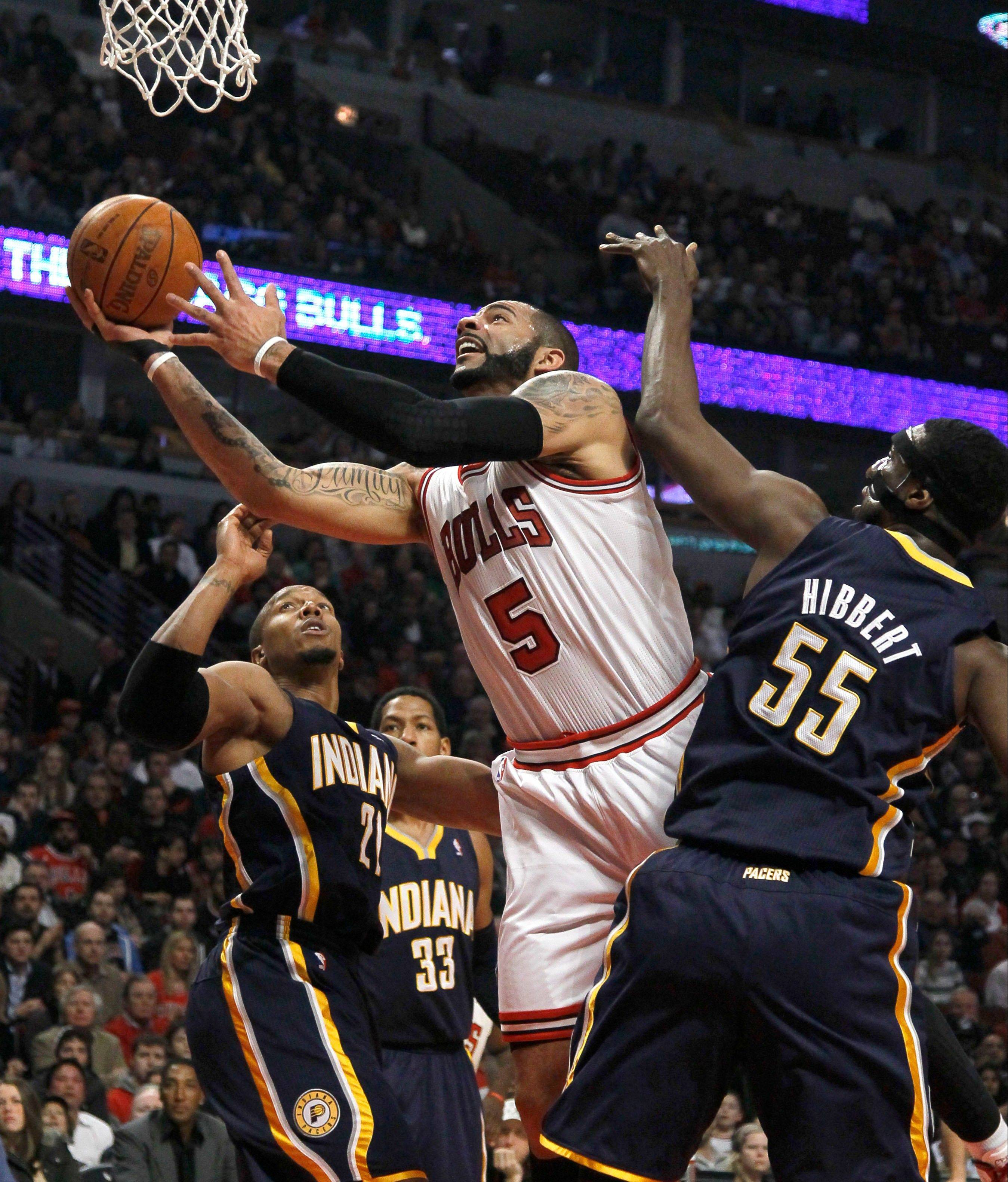 The Bulls' Carlos Boozer scores past the defense of Indiana Pacers forward David West (21) and center Roy Hibbert (55), during the first half on Wednesday at the United Center.