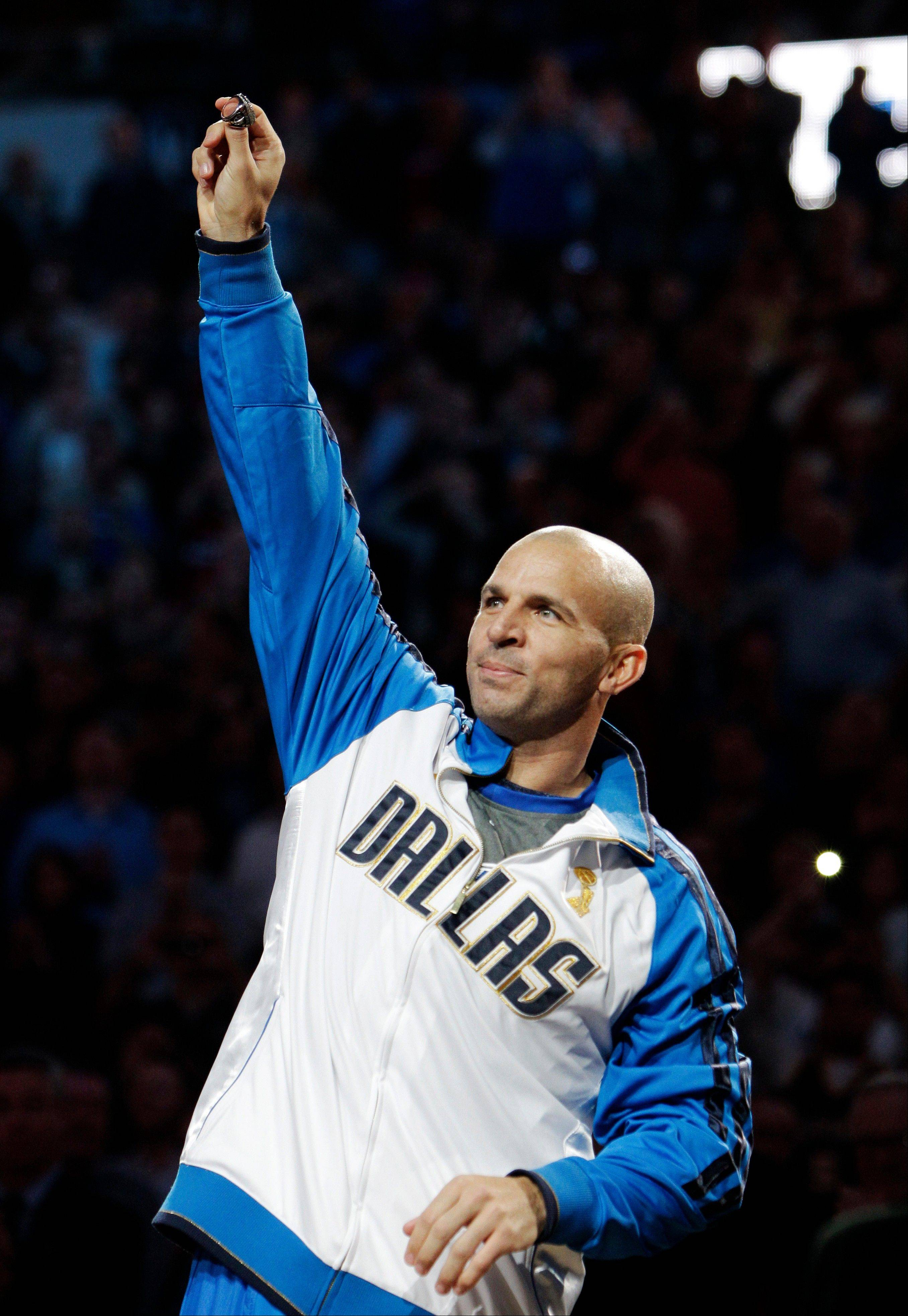 The Mavericks' Jason Kidd holds up his diamond-encrusted NBA championship ring before Wednesday night's home game against Minnesota