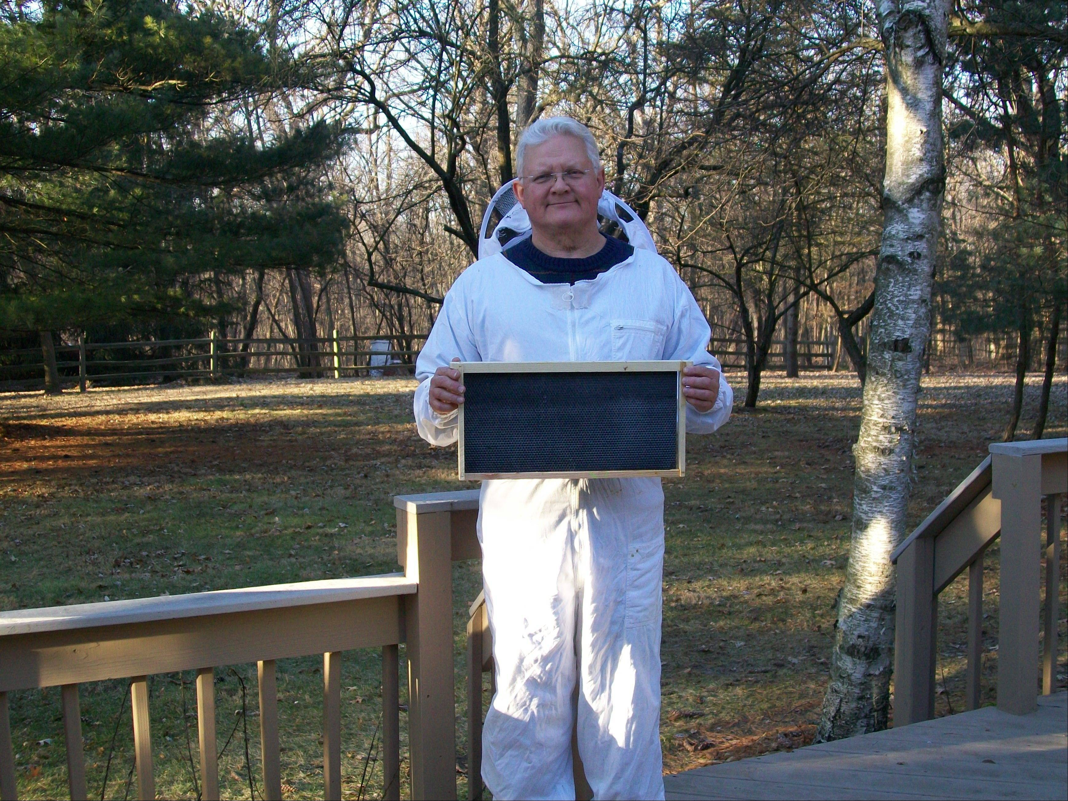 Beekeeper Hillard Bryant displays a frame that's inserted into a box where bees produce and store honey -- all in Bryant's backyard.