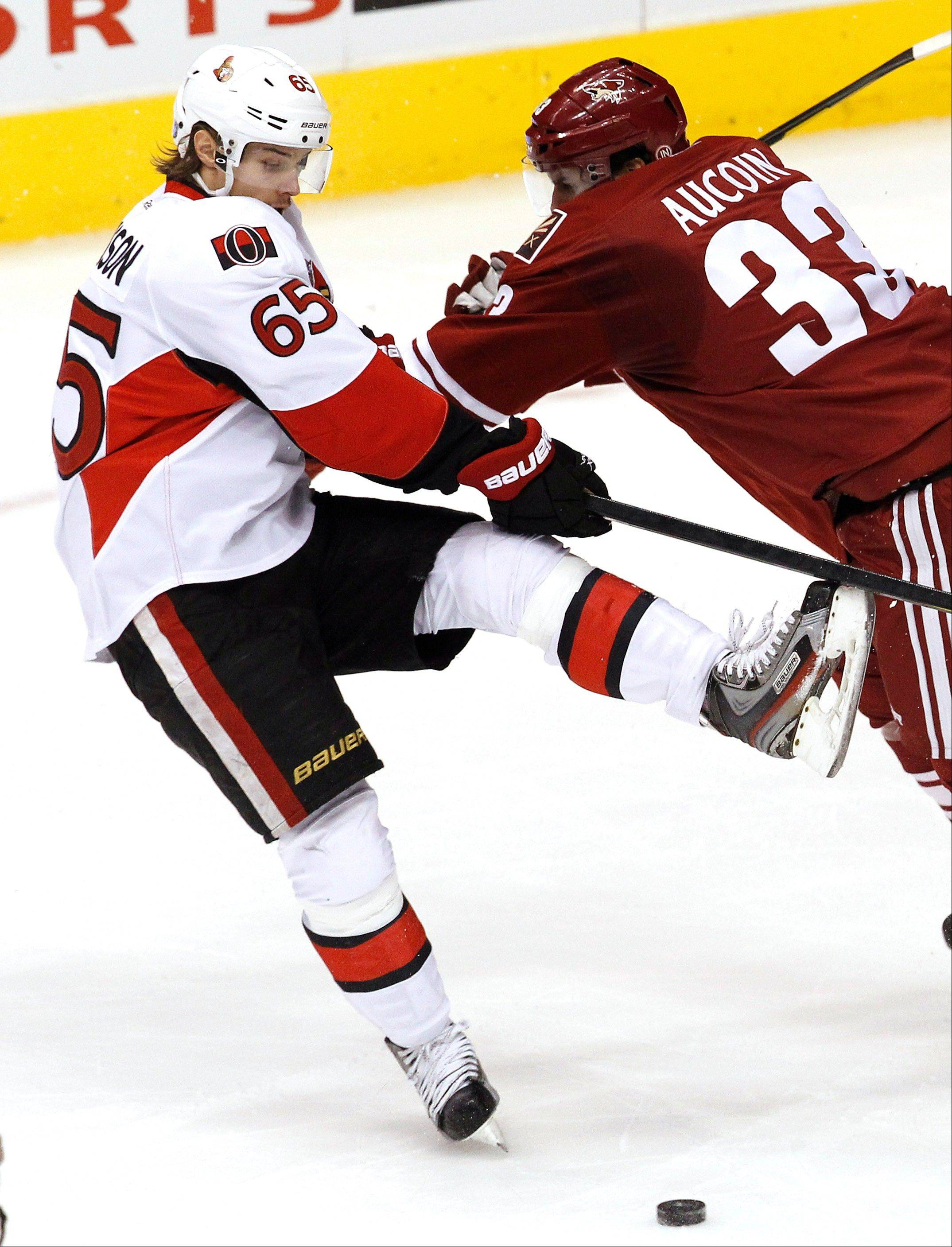 Phoenix's Adrian Aucoin checks Ottawa Senators' Erik Karlsson in a game on Tuesday. Karlsson was the first player chosen by Daniel Alfredsson, who is one of the captains for Sunday's NHL All-Star Game.