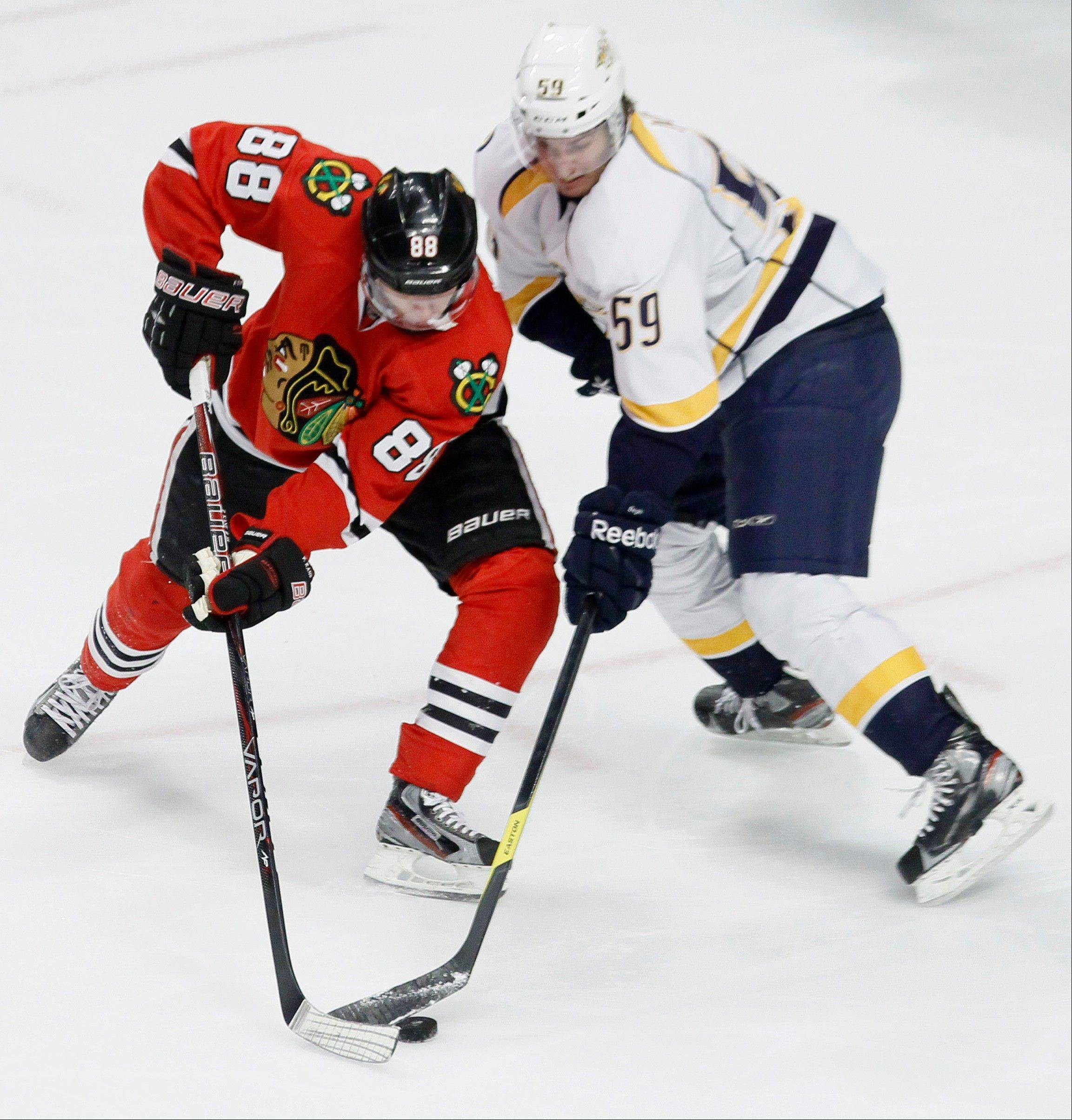 Chicago Blackhawks right wing Patrick Kane (88) takes a backhand shot on goal as Nashville Predators defenseman Roman Josi (59) reaches for the puck during the second period of Tuesday's game.