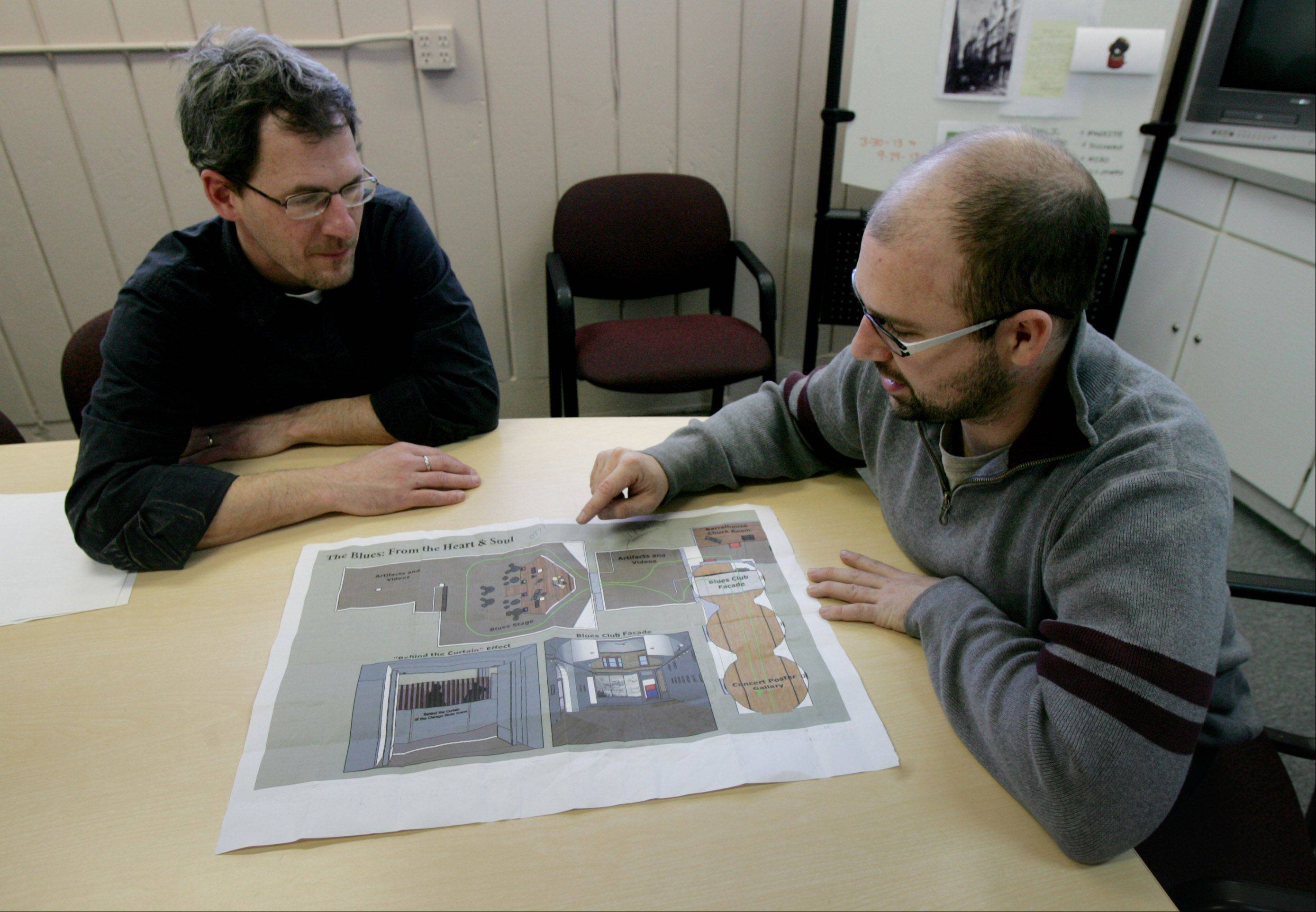 Steve Furnett, left, and Justin Collins review the layout for the gallery for the exhibit.