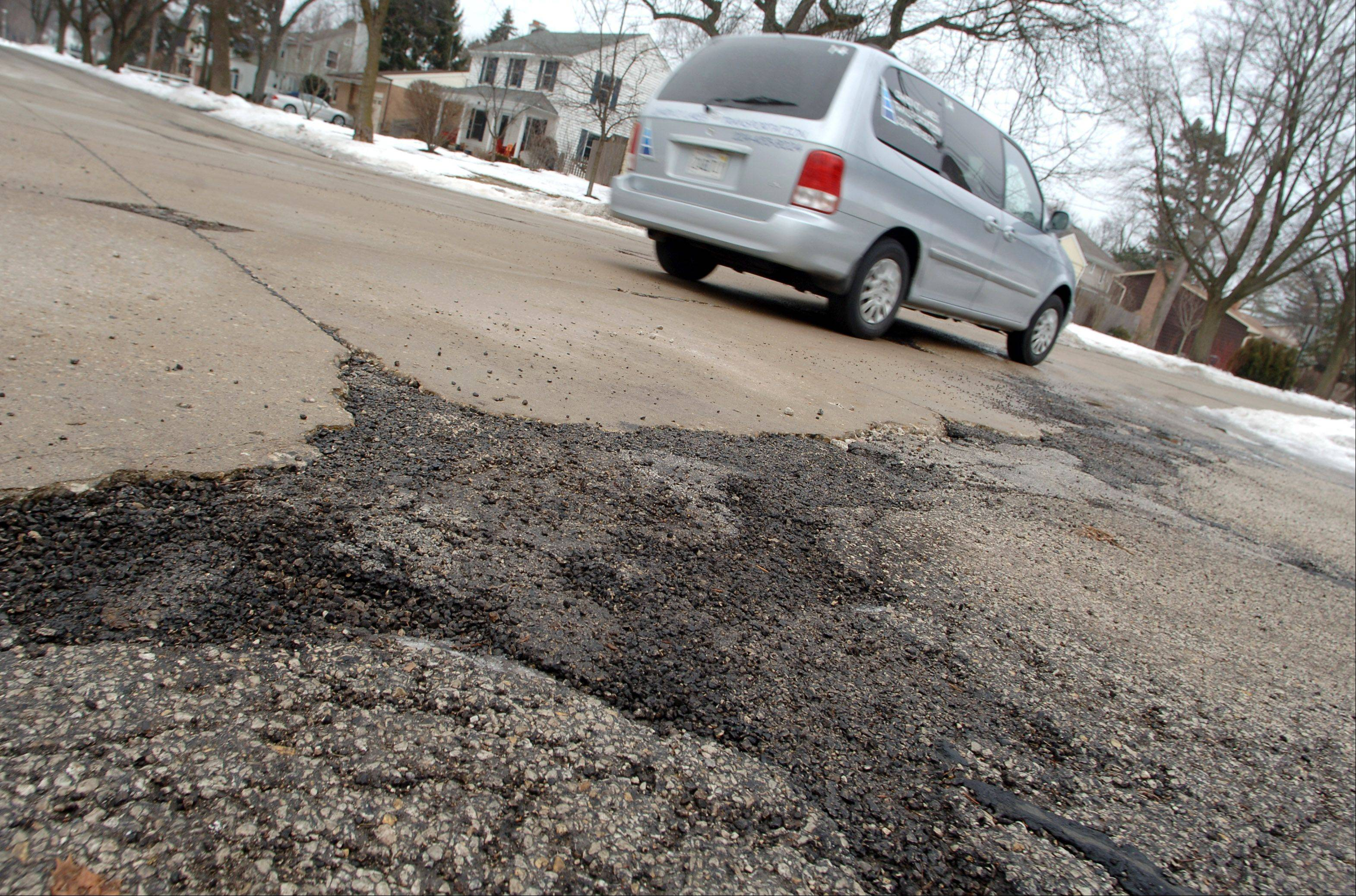A driver passes through a well-patched intersection of West Rockland Road and Burdick Street in Libertyville. Voters soon will receive information on a village request to approve a tax increase to pay for road repairs.