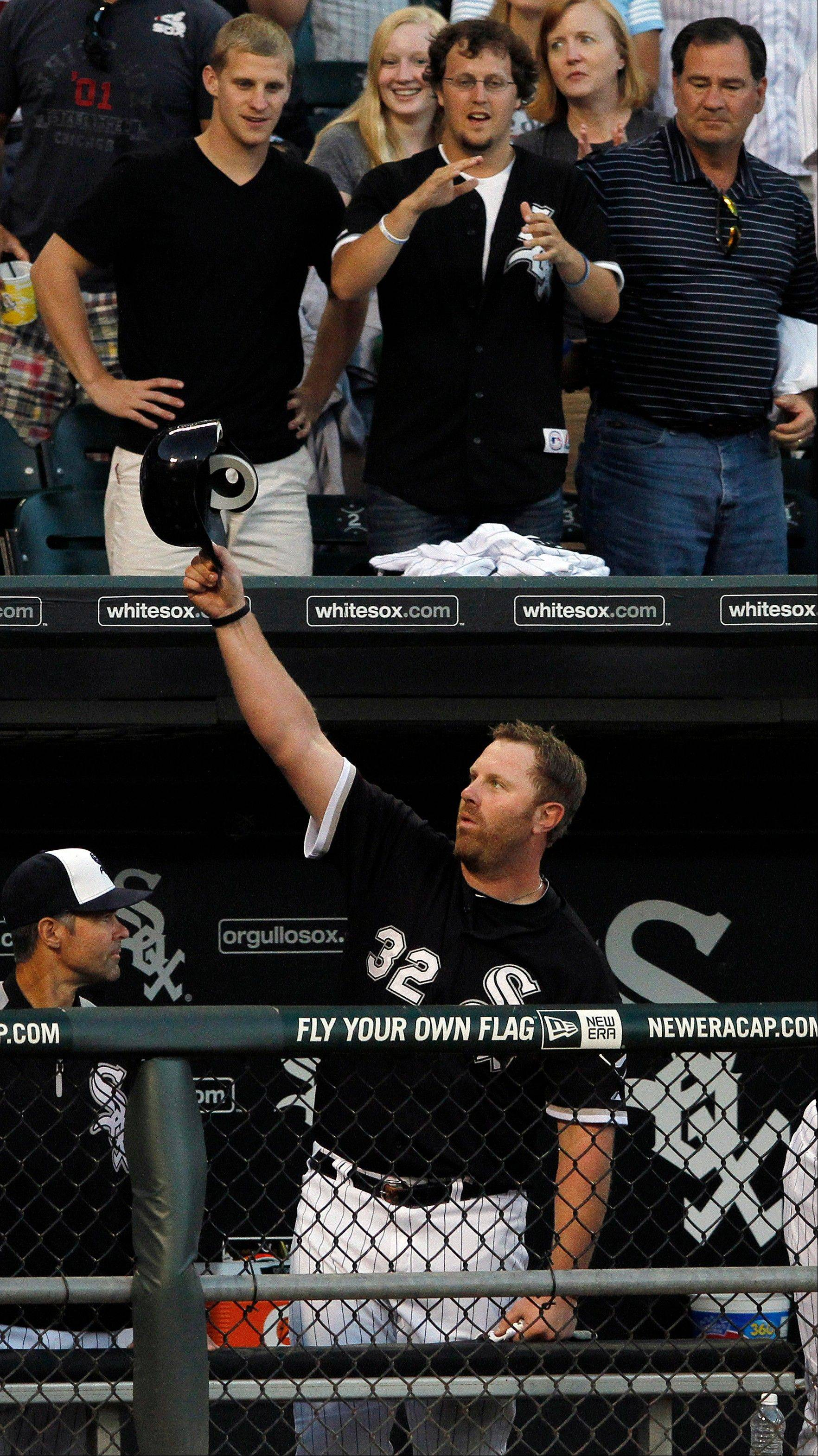 Chicago White Sox's Adam Dunn lifts his batting helmet to the crowd after hitting a two-run home run against the Kansas City Royals.