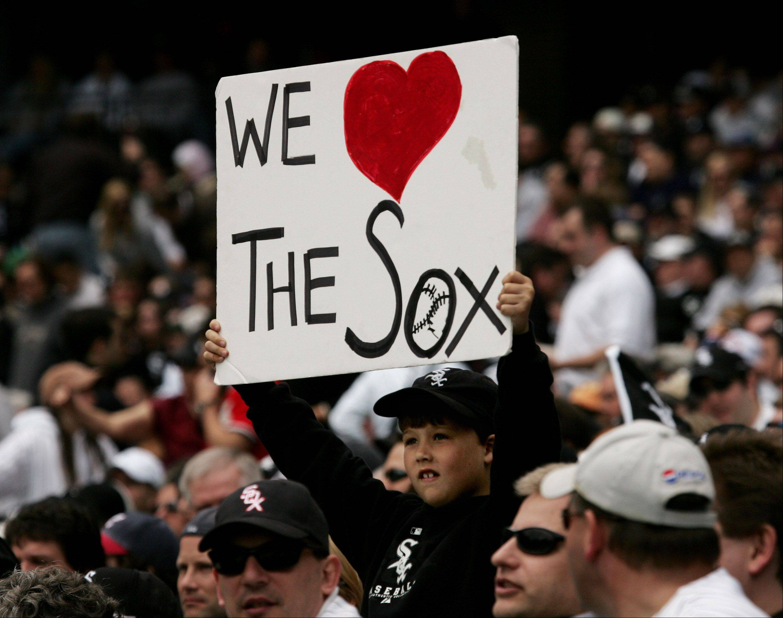 A young fan holds up a sign showing his support for the team during the Chicago White Sox opening day.