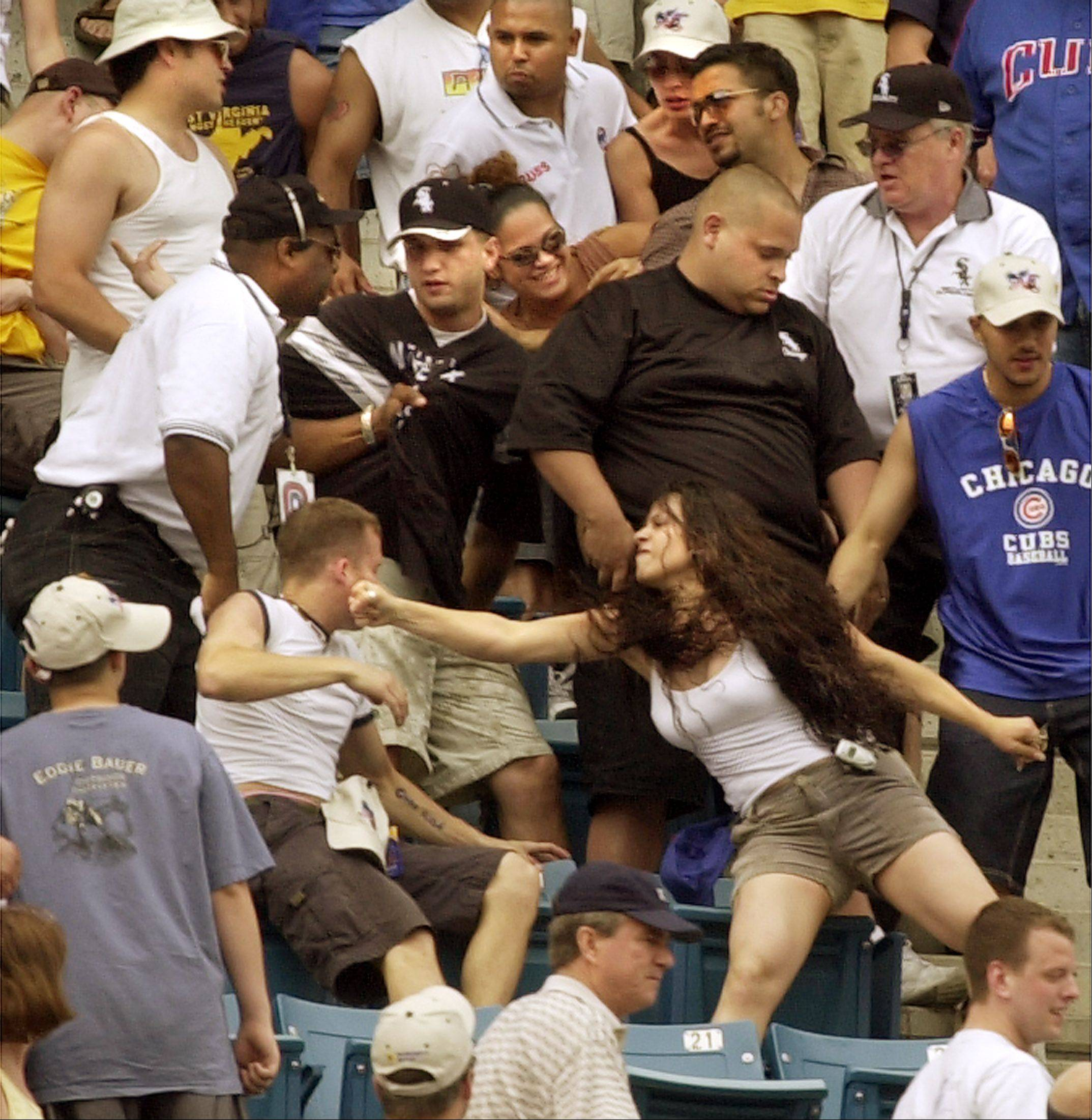 A US Cellular Field Security official has his hands full with two fighting men when a woman lunges to punch one of the men during the interleague game between the White Sox and the Cubs game. Several fights broke out during the game and several people were ejected.