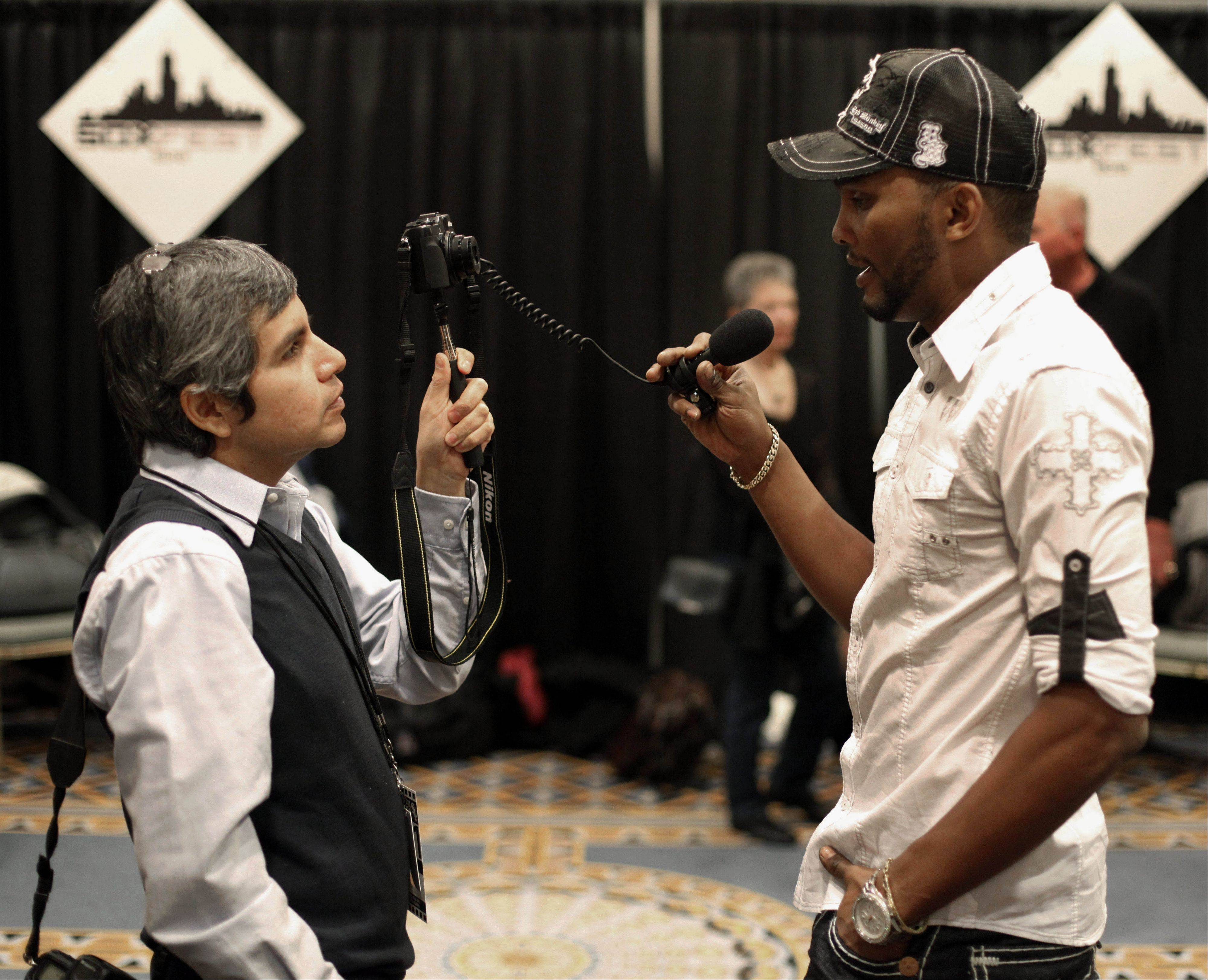 Chicago White Sox baseball shortstop Alexei Ramirez, right, holds a microphone during an interview at the White Sox Fan Fest.