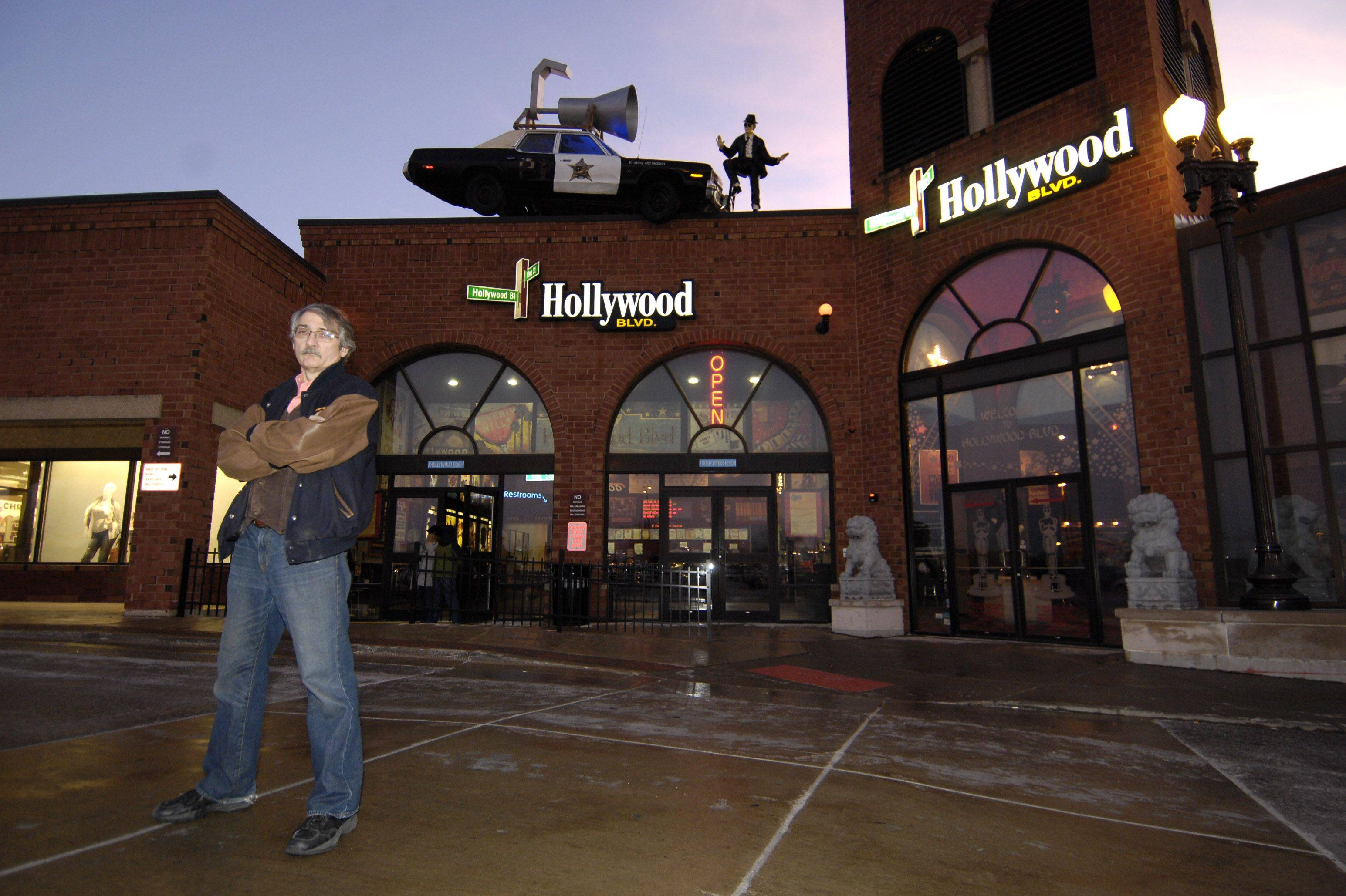 "A car from the ""Blues Brothers"" movie adorns the top of Ted Bulthaup's Hollywood Blvd. theater in Woodridge."