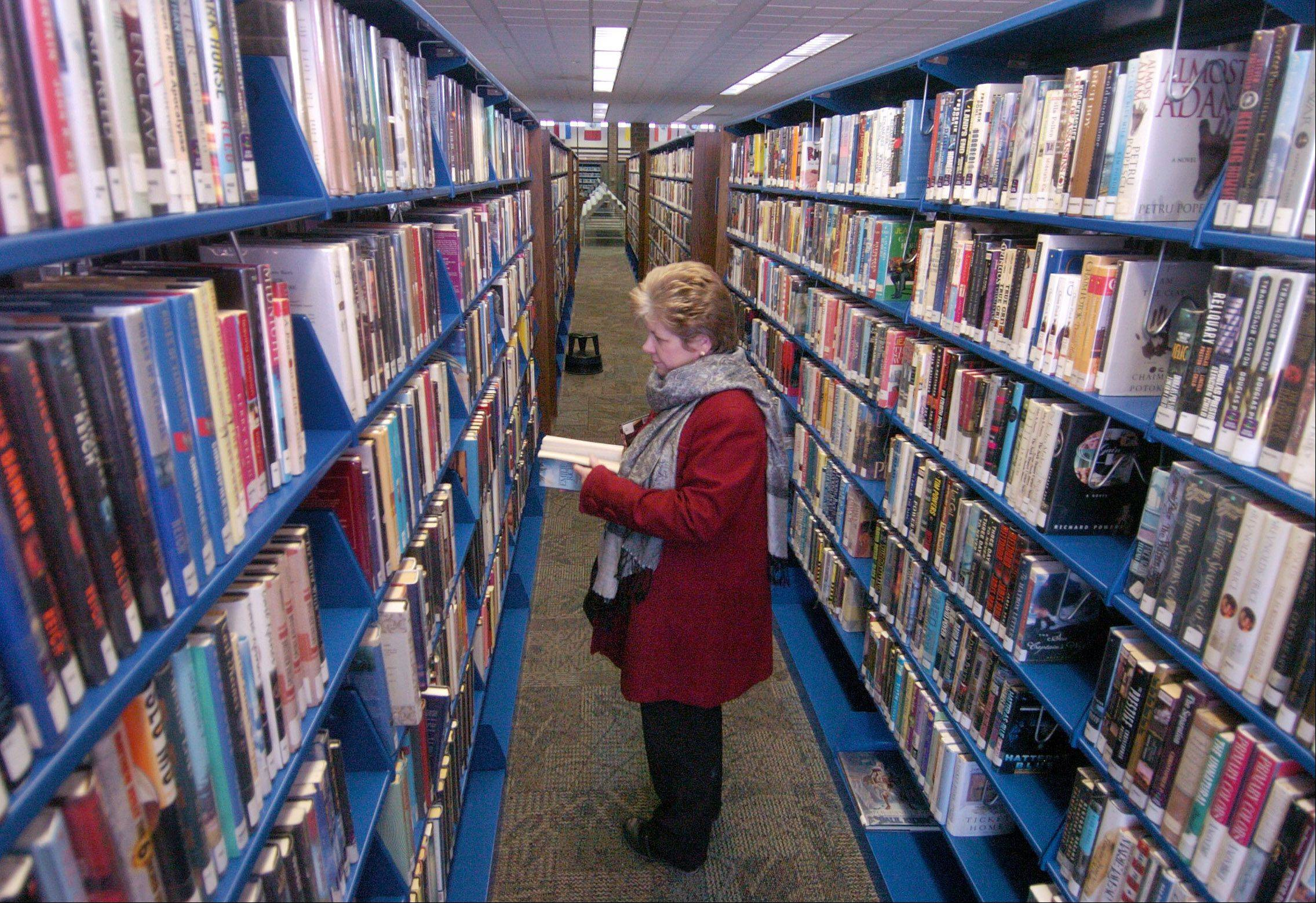 Lynn Thurman of Elk Grove Village picks out some fiction in the Elk Grove Village Library. As of May 1st, residents west of Rohlwing Road will lose their Elk Grove Village library cards because a tax-sharing deal between the Schaumburg and Elk Grove library districts is being canceled.