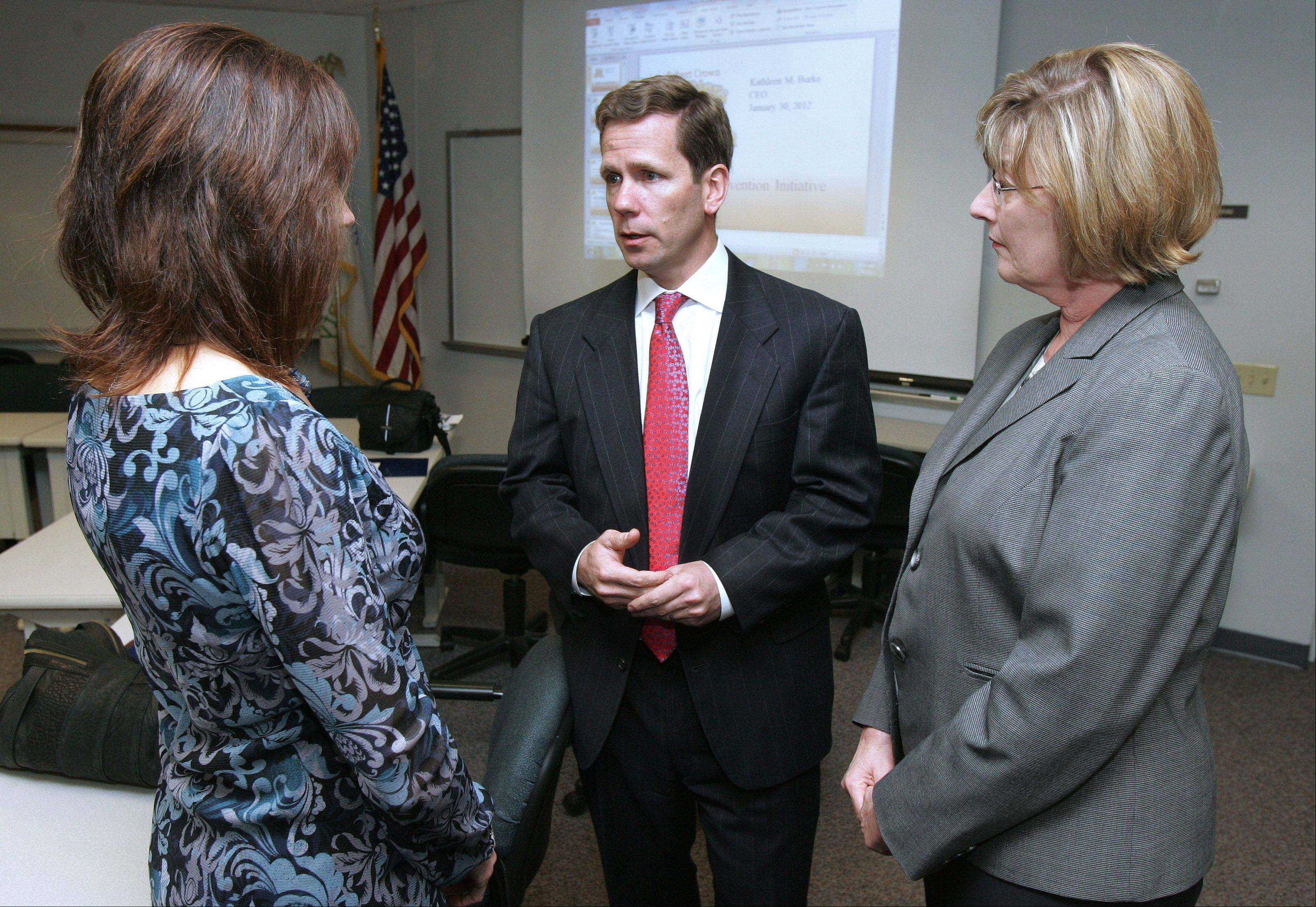 U.S. Congressman Robert J. Dold talks to Michelle Hines, of Hearts of Hope, left, and Irene Pierce, executive director of the Lake County Health Department, before the start of a round-table discussion on the dangers of heroin. The session Monday in Lake County was attended by local school, law enforcement, and substance abuse authorities.