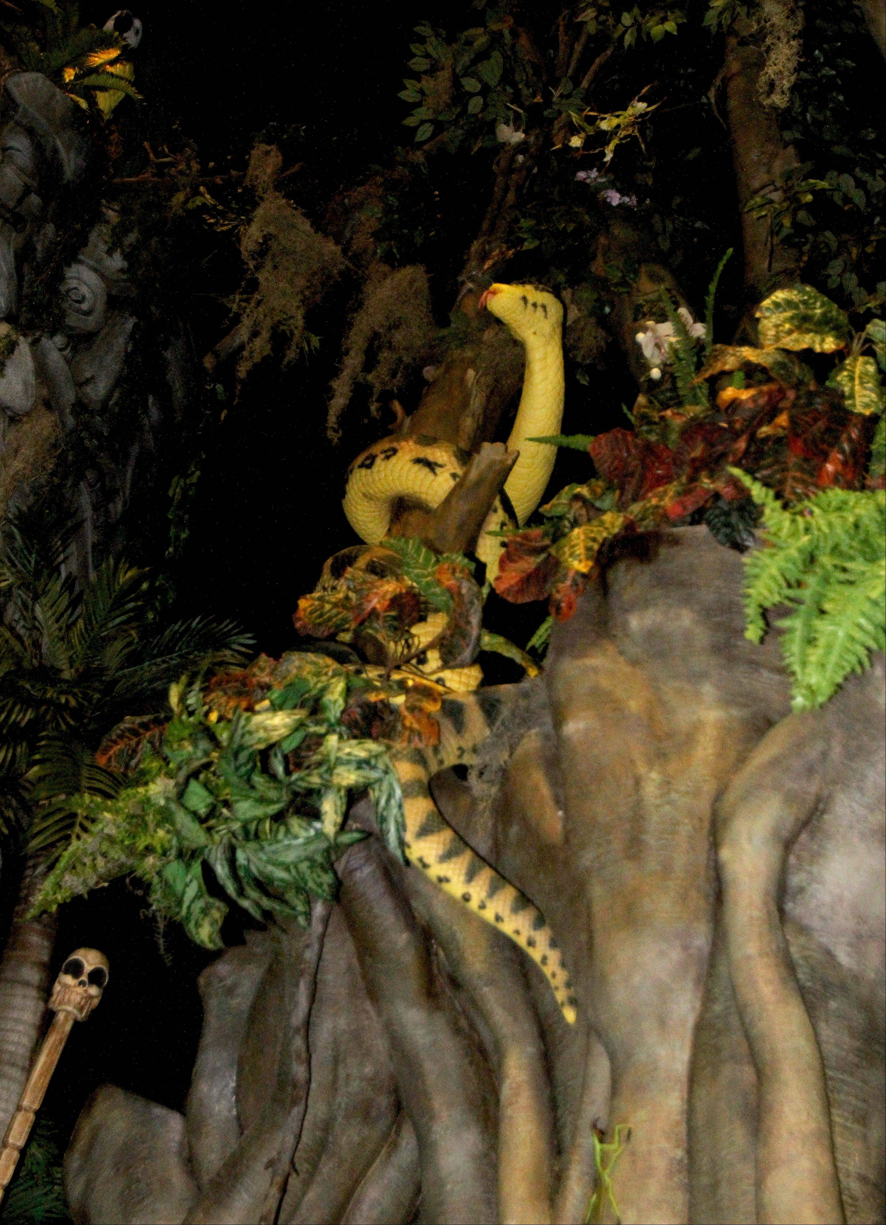 A snake crawls up a tree in the Mayan themed theater at the Hollywood Palms Cinema in Naperville.