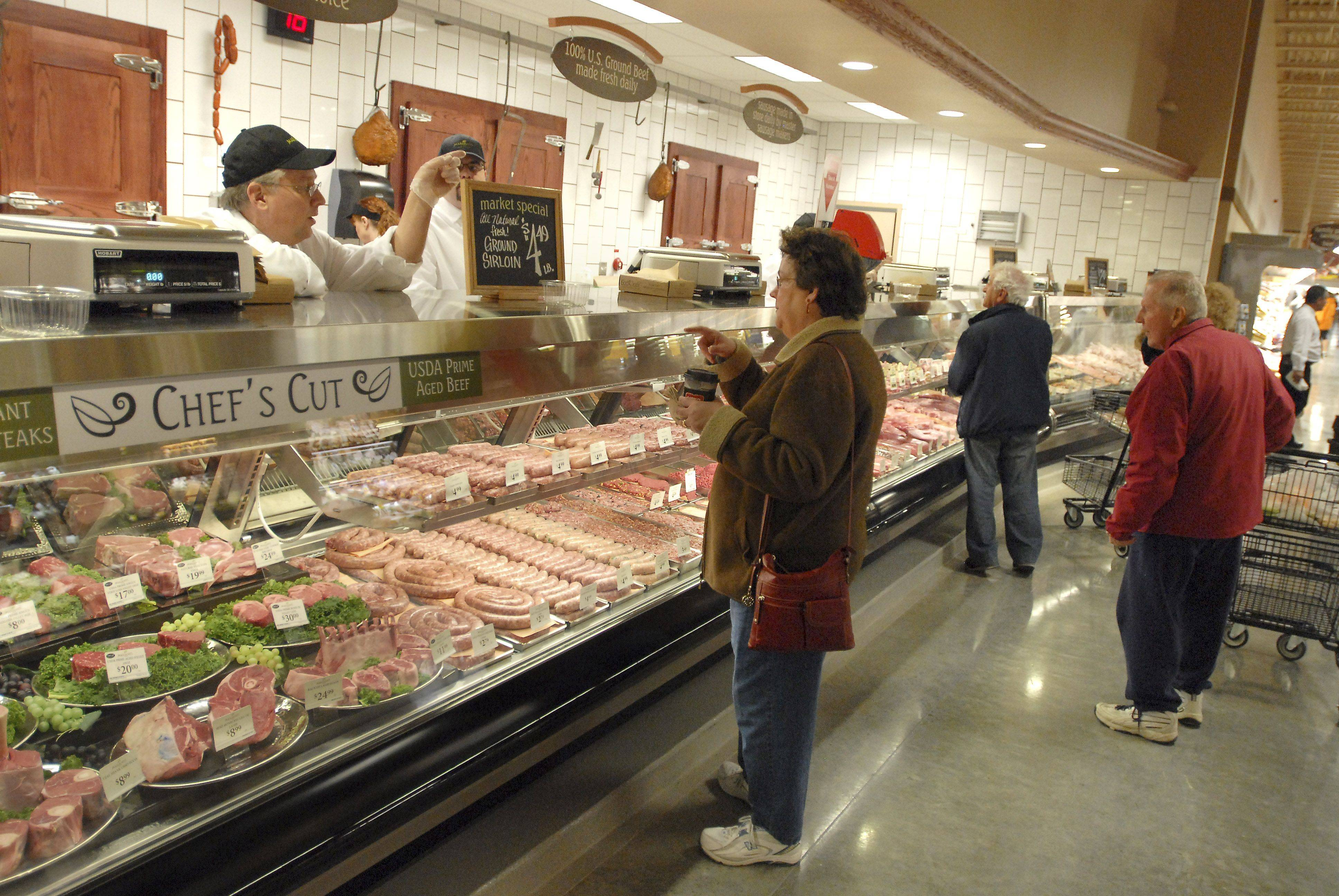 Butchers give advice to customers at the meat and seafood department during the grand opening of Mariano's Fresh Market Tuesday in Palatine.