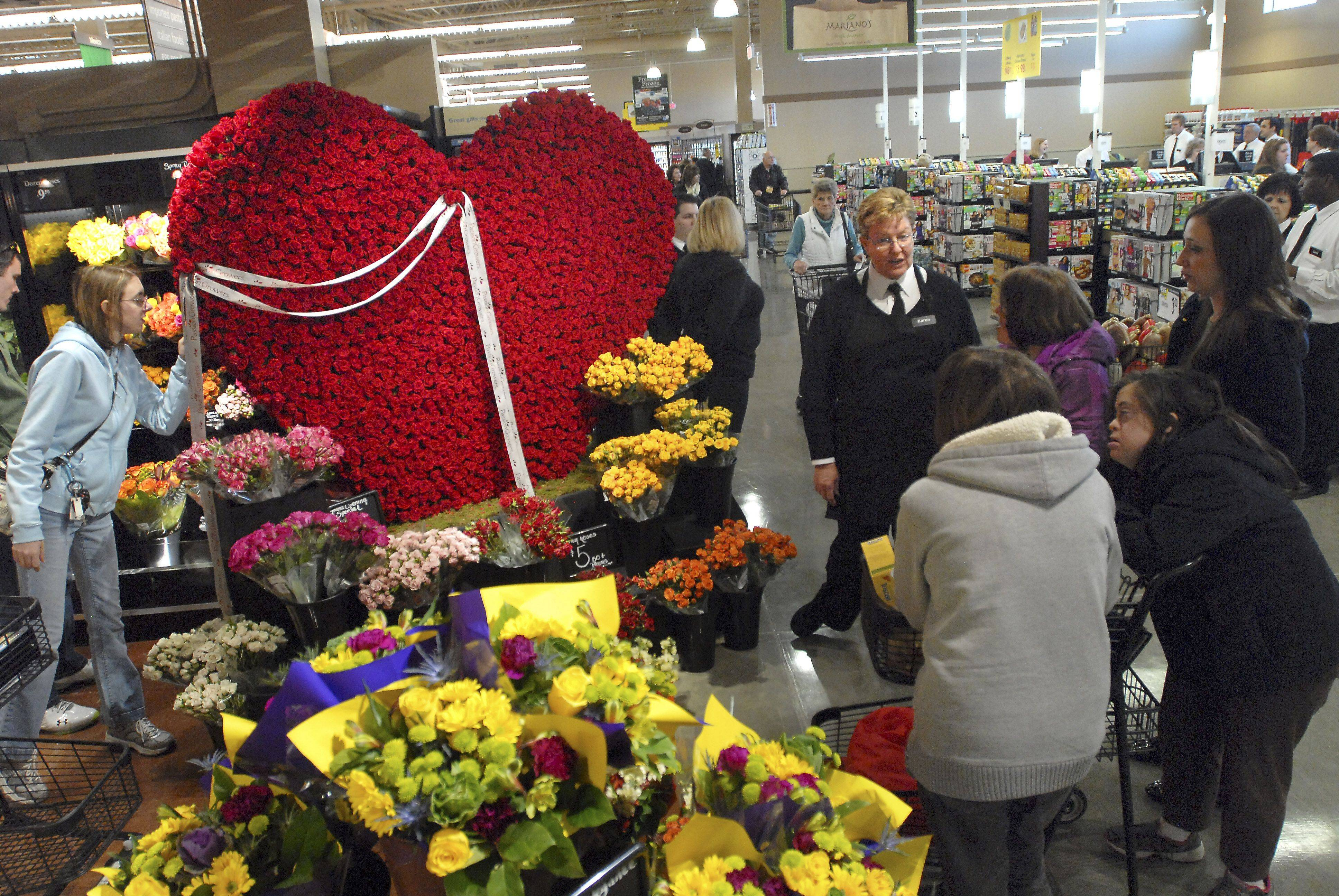 Floral department manager Karen Kunz, right, tells customers about the giant Valentine's Day display made of Forever Roses during the grand opening of Mariano's Fresh Market Tuesday in Palatine.