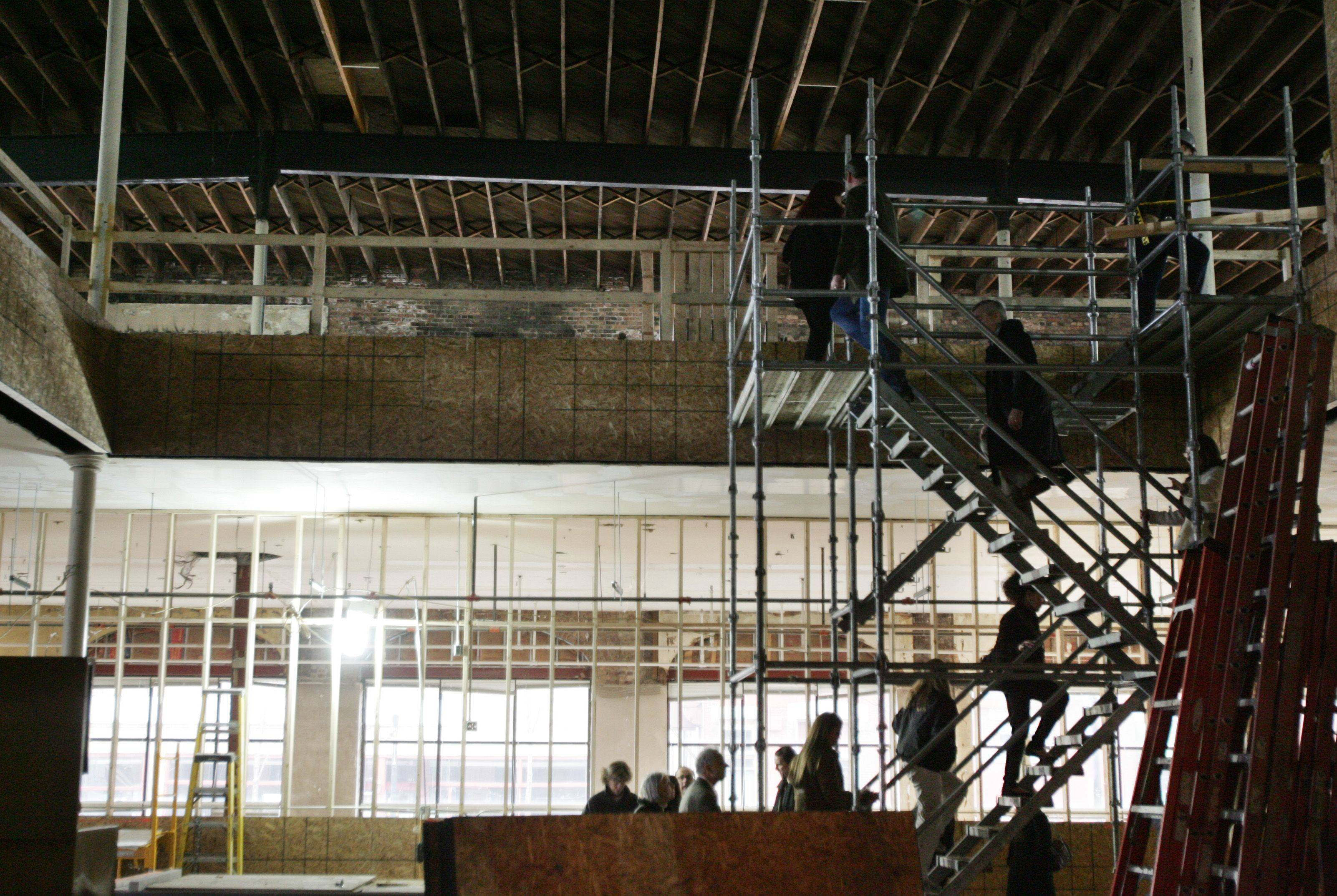 Guests climb a large set of scaffolding as they head to the second floor during the Artspace tour Tuesday in Elgin.