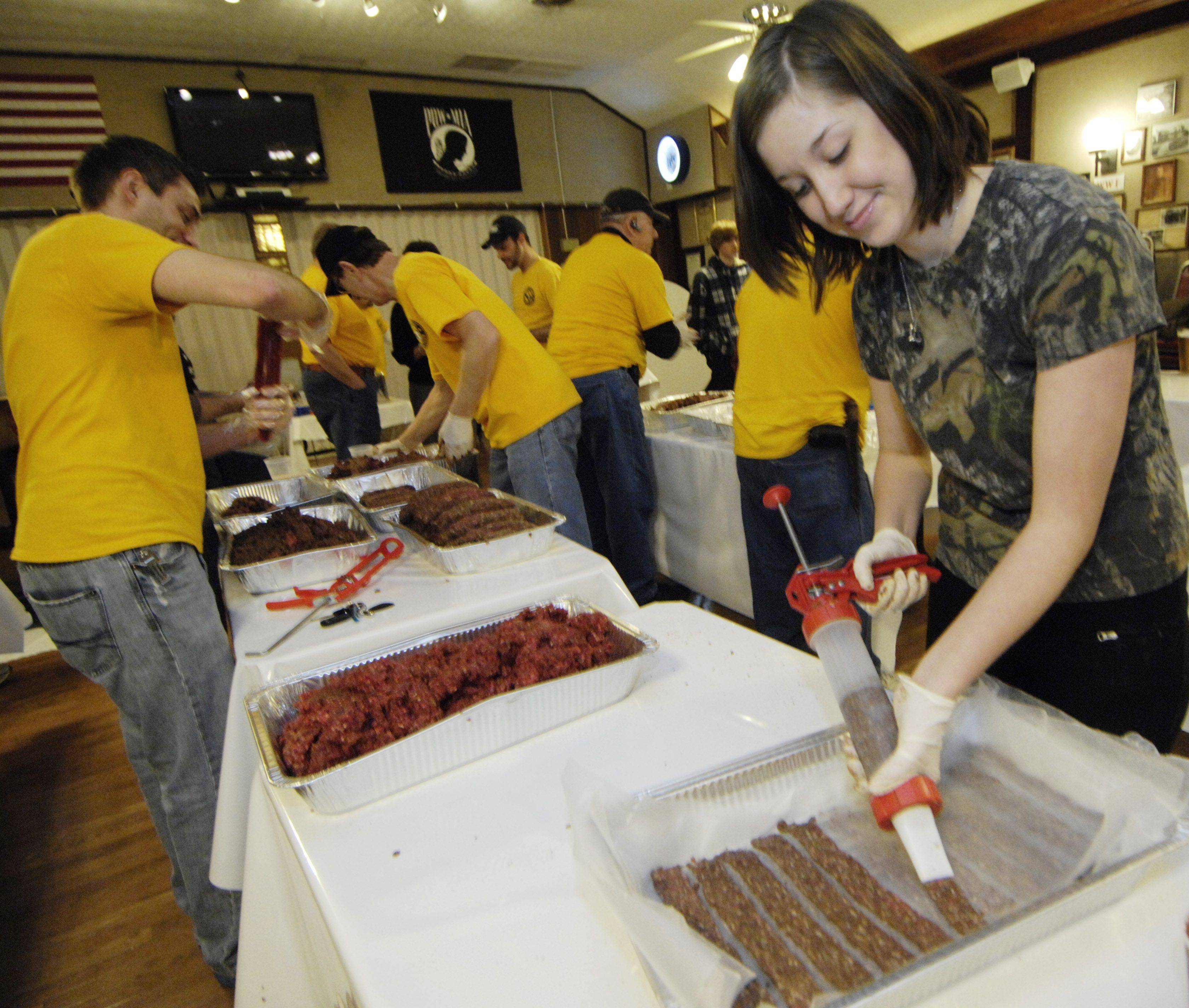 Sara Belcher of Union, Ill., helps prepare spicy jerky made from fresh venison.