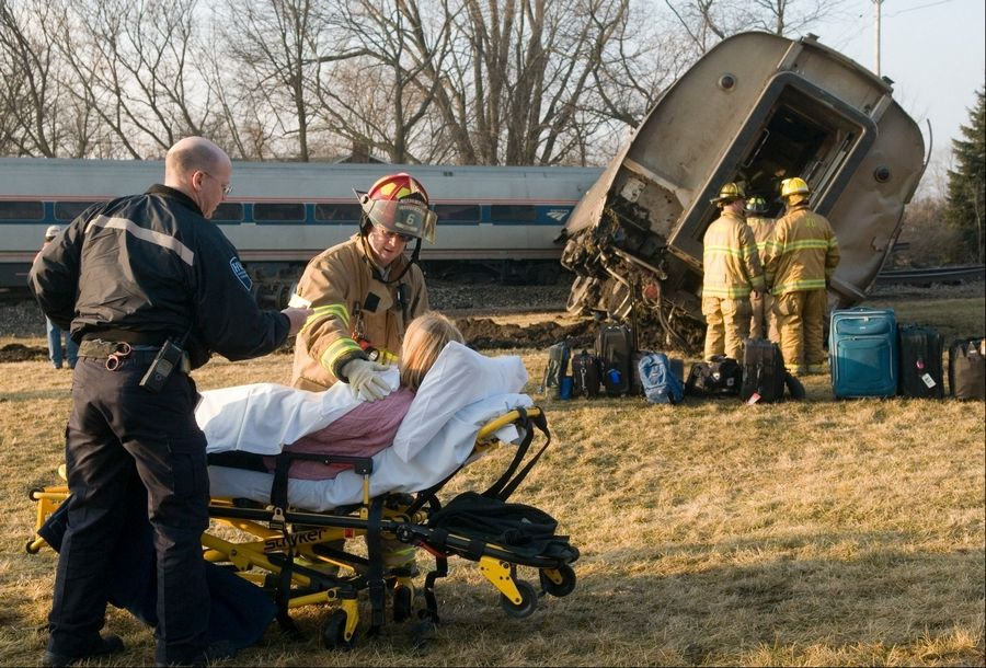 Rescue workers help an injured woman at the scene of a train derailment in Leoni Township, Mich., Wednesday. A Chicago-bound Amtrak passenger train derailed after crashing into a semitruck at a highway crossing.