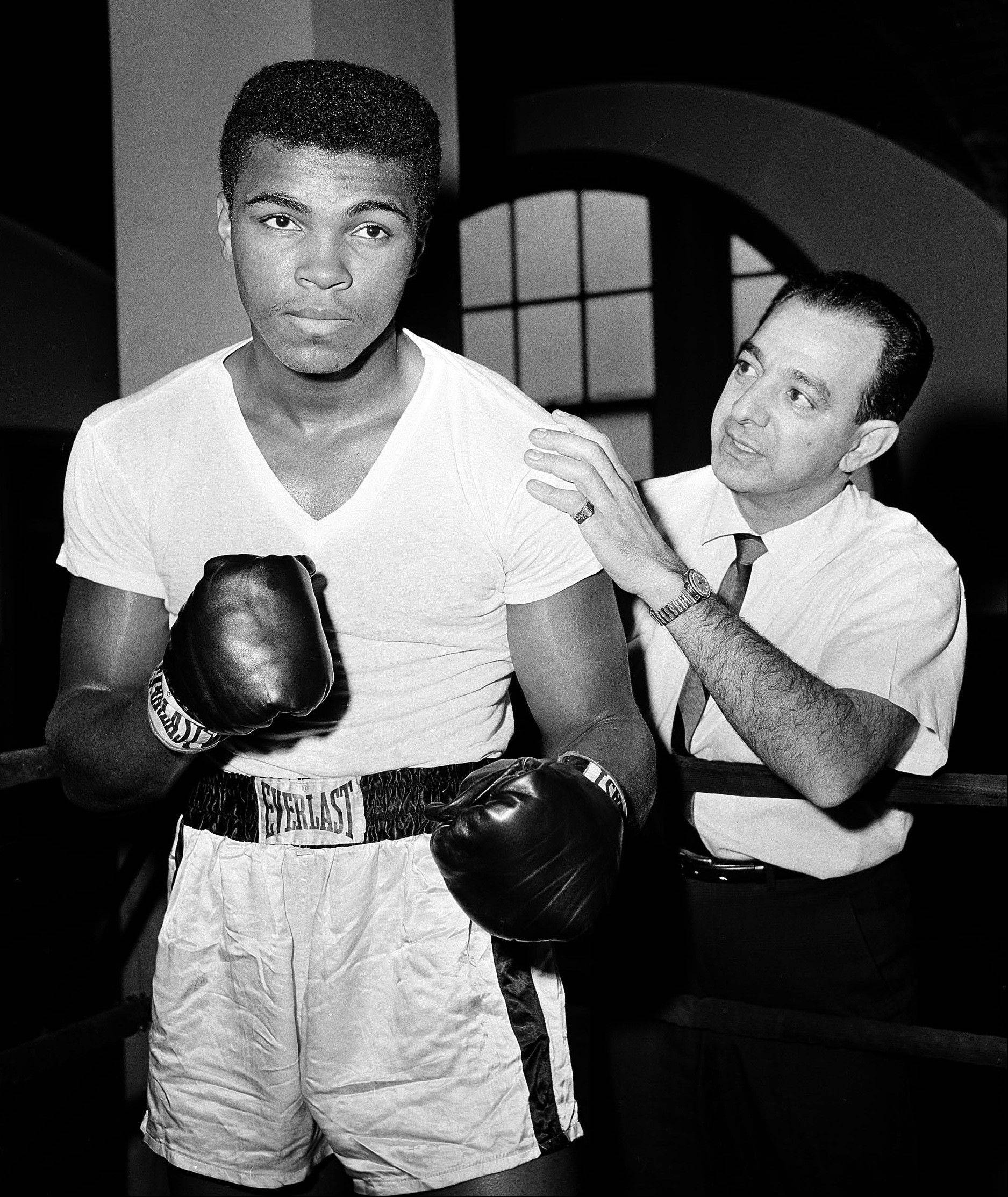 A young Muhammad Ali, left, stands with trainer Angelo Dundee at City Parks Gym in New York in 1962.
