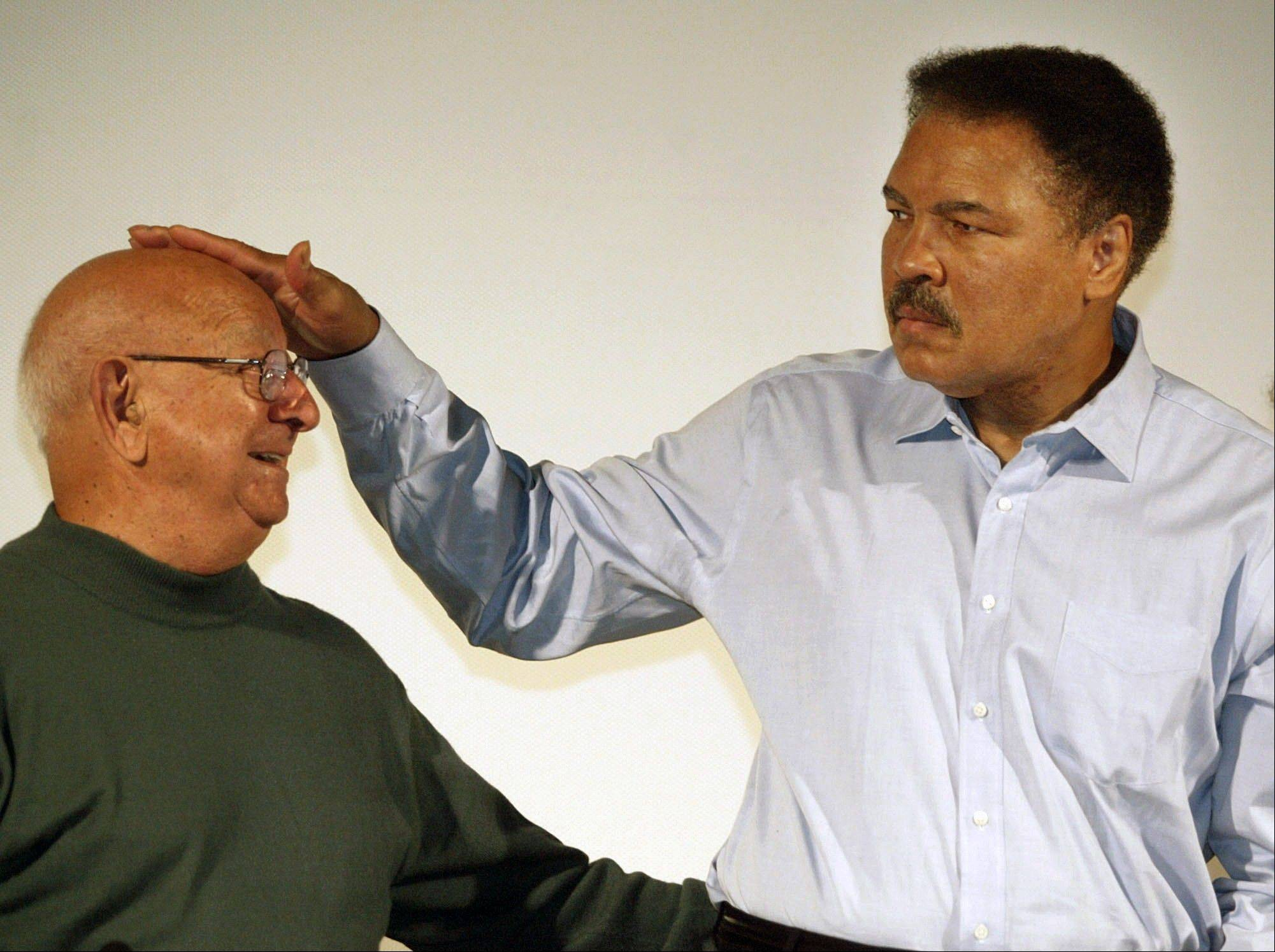 Boxing great Muhammad Ali touches the head of former coach Angelo Dundee at the Book Fair in Frankfurt, Germany, in 2003. Dundee, who helped groom Ali and Sugar Ray Leonard into world champions and became one of boxing's most recognizable figures, died Wednesday.