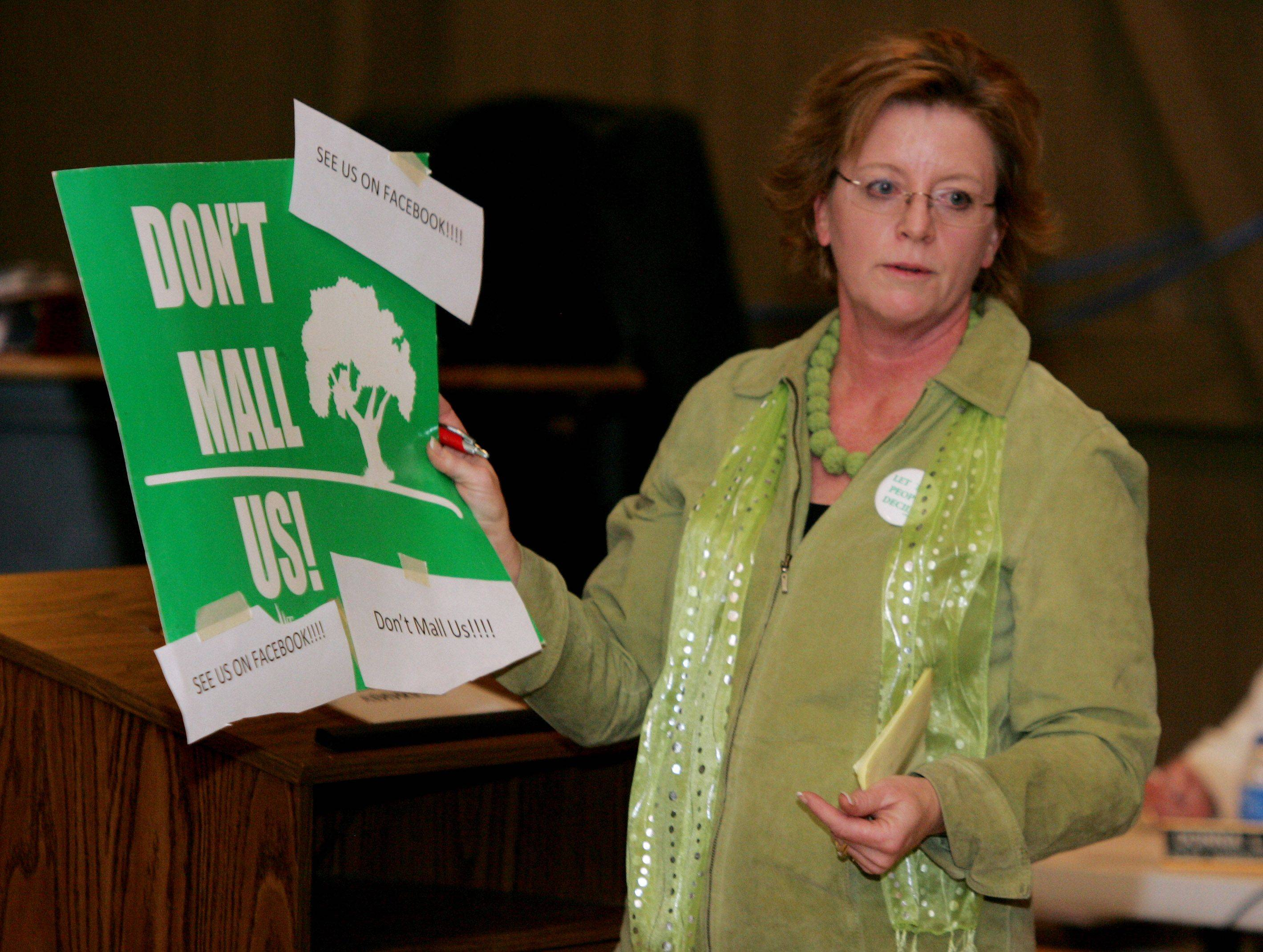 Diane Benz of the Valentine Manor subdivision holds up an old sign as she criticizes the plan for a shopping center during a special Hawthorn Woods village board meeting Thursday to discuss Lake County's rezoning of the Dimucci property for a shopping center.