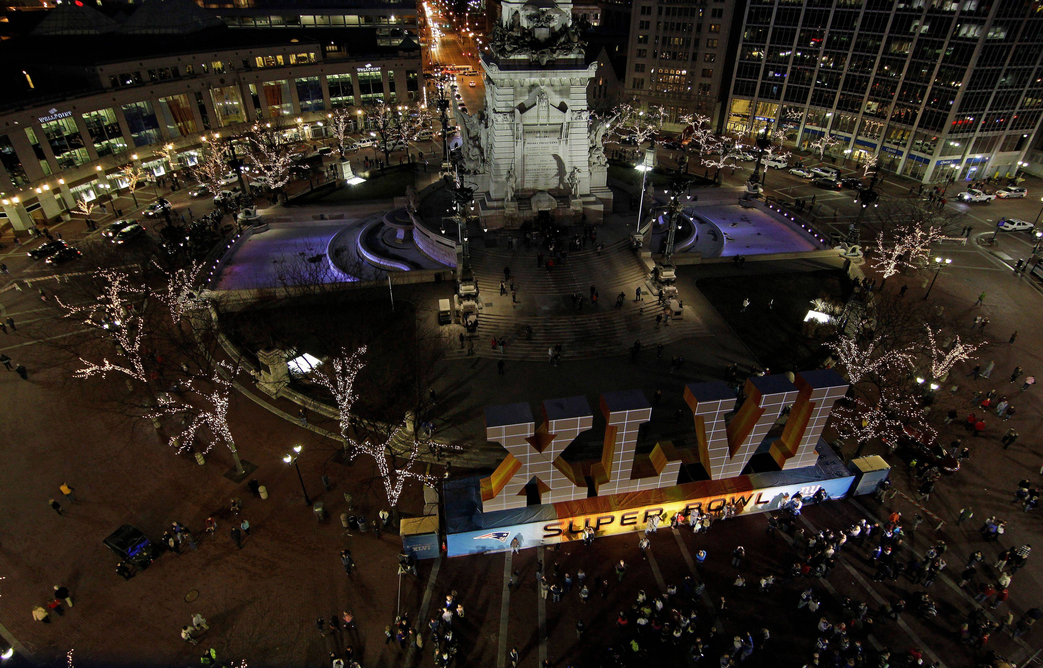 Fans have their photos taken in front of NFL football's Super Bowl XLVI sign on Monument Circle in Indianapolis. Indianapolis will become a celebrity hub over the next few days leading up to Sunday's Super Bowl.