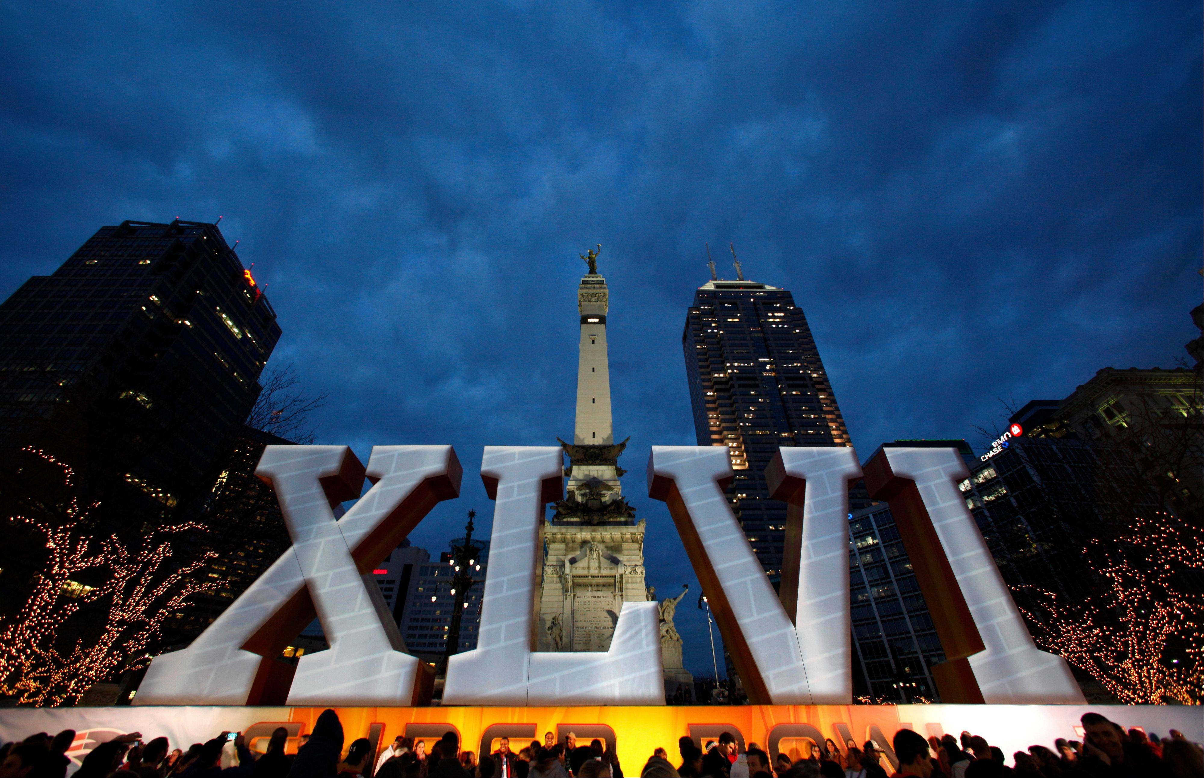 People crowd around the Super Bowl XLVI sign Friday on Monument Circle in Indianapolis. The New England Patriots are scheduled to face the New York Giants in NFL football's Super Bowl XLVI on Sunday.