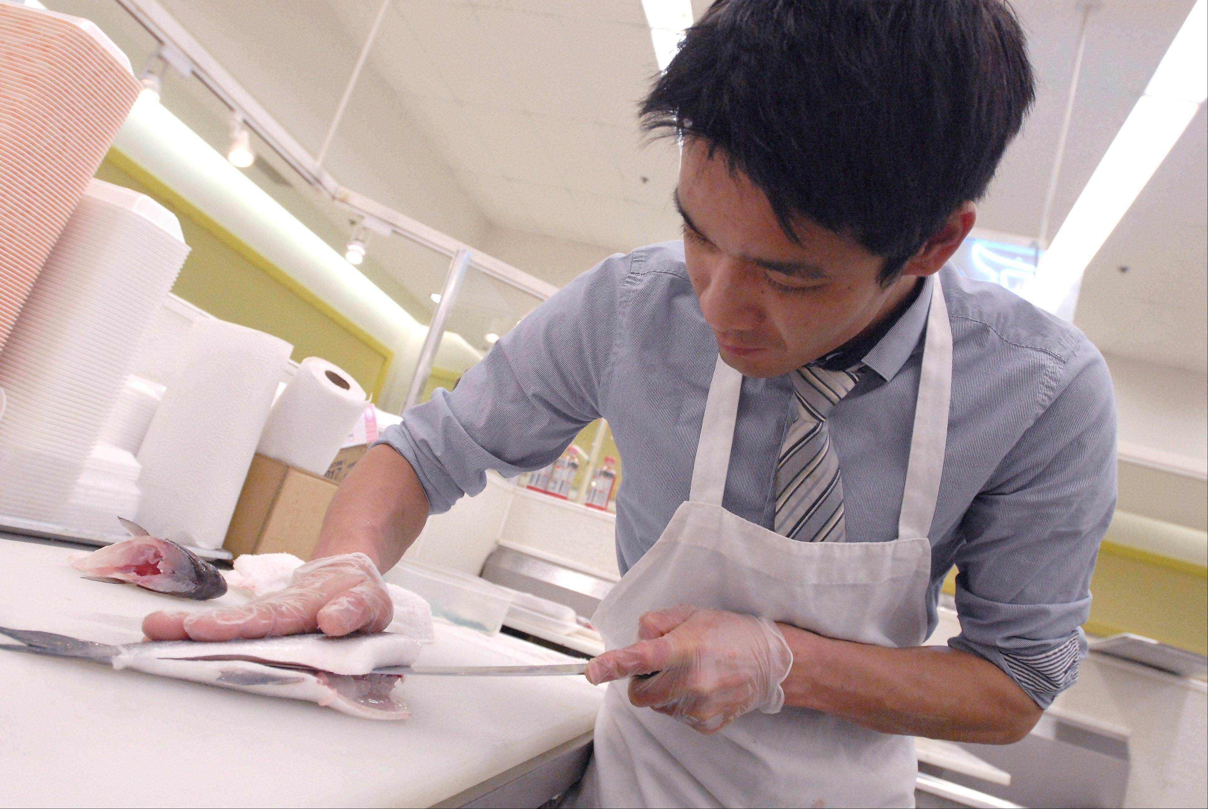 Mitsuwa Marketplace assistant store manager Atsushi Koike cuts a piece of loup de mer, a type of sea bass for the sashimi department. The Arlington Heights store, which flies in their fish, sells about 150 pounds of tuna every day.