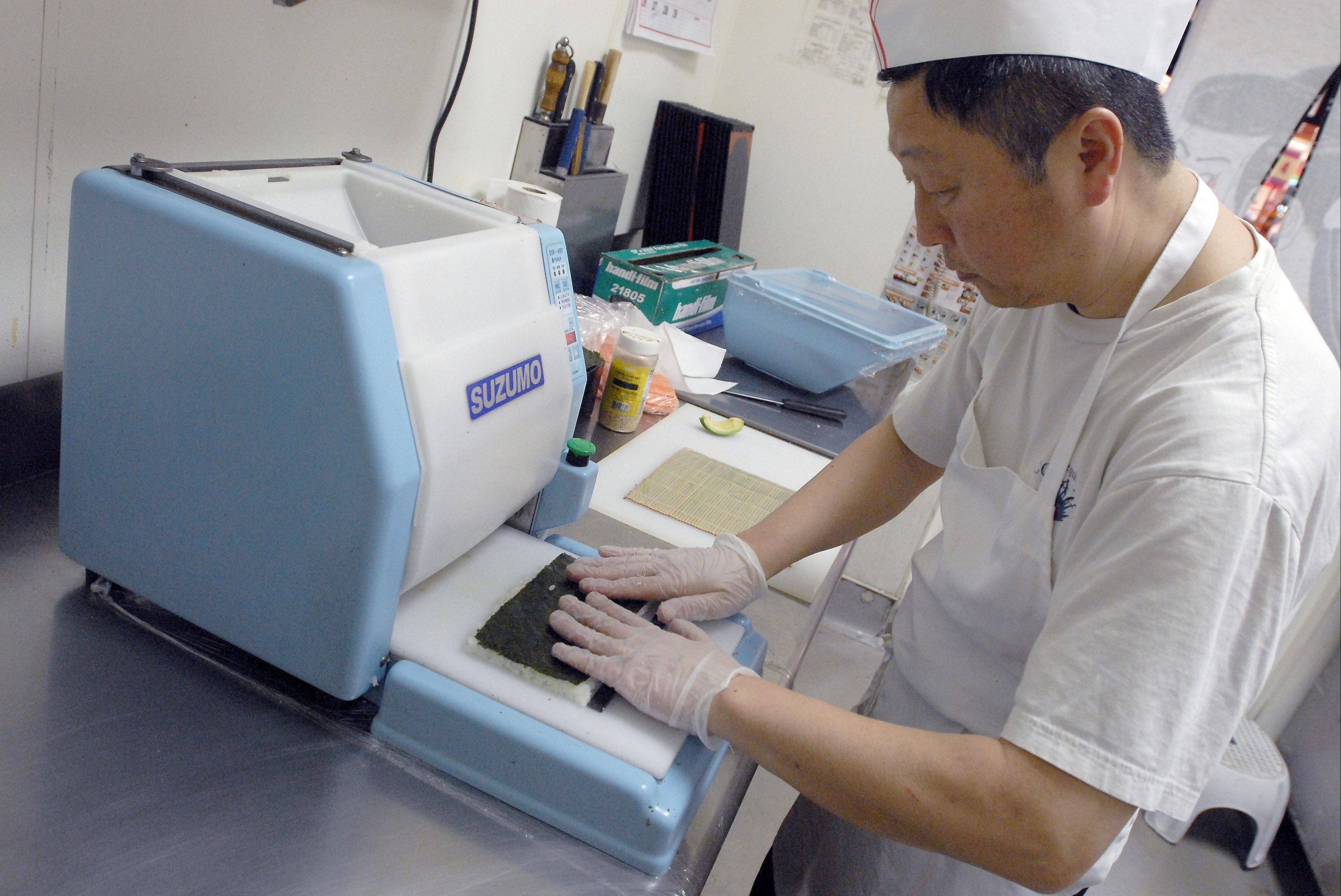 Sushi department supervisor Satoshi Tsutsumi applies seaweed to a sheet of rice made by machine to speed production of sushi.