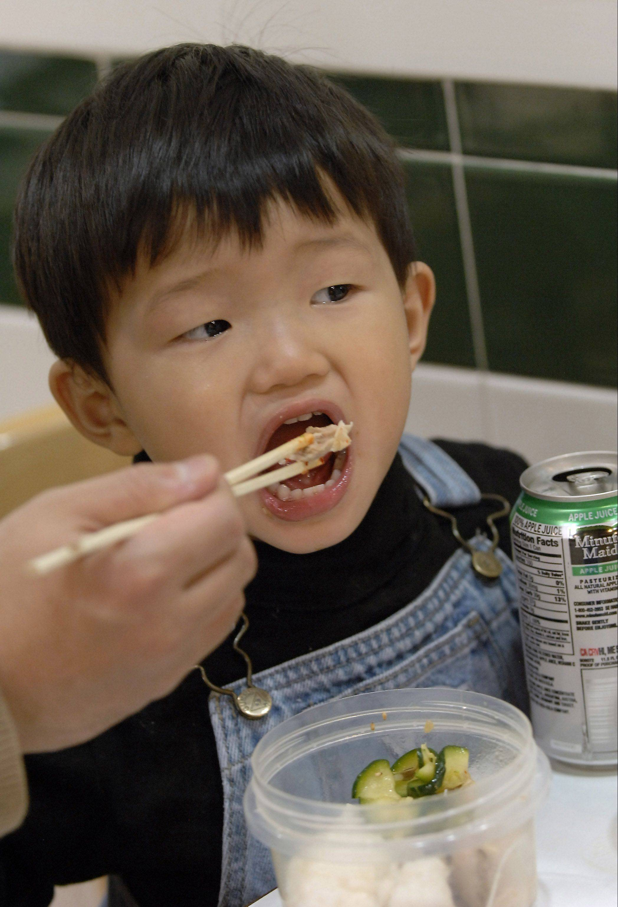 Yoshiharu Kawamoto, 2, gets help with chopsticks from his father Yoshimizu Kawamoto while eating food from Mama House in the food court.