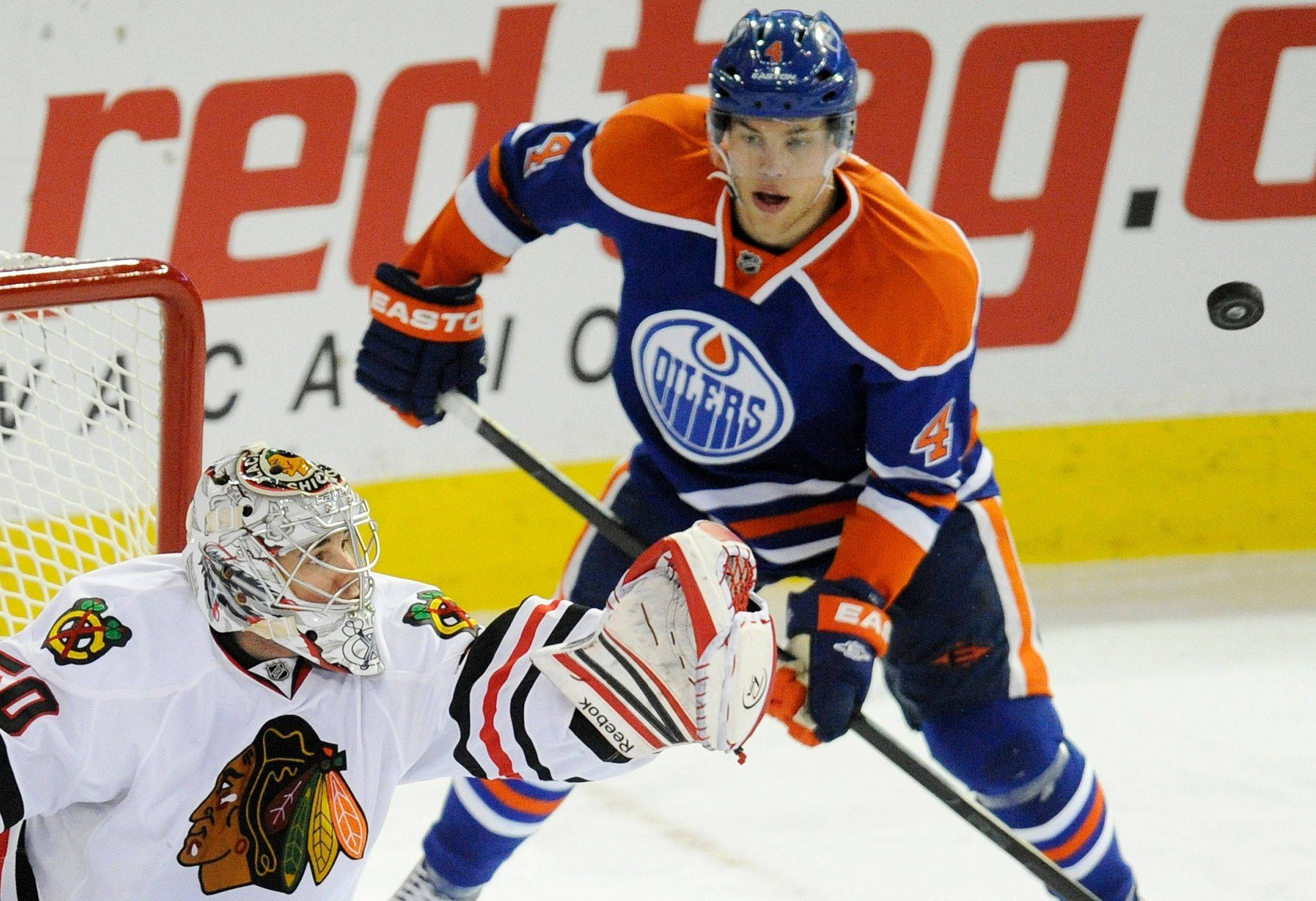 Edmonton Oilers' Taylor Hal, right, watches Chicago Blackhawks goalie Cory Crawford make a save during the second period of NHL hockey game action in Edmonton, Alberta, on Thursday, Feb. 2, 2012.