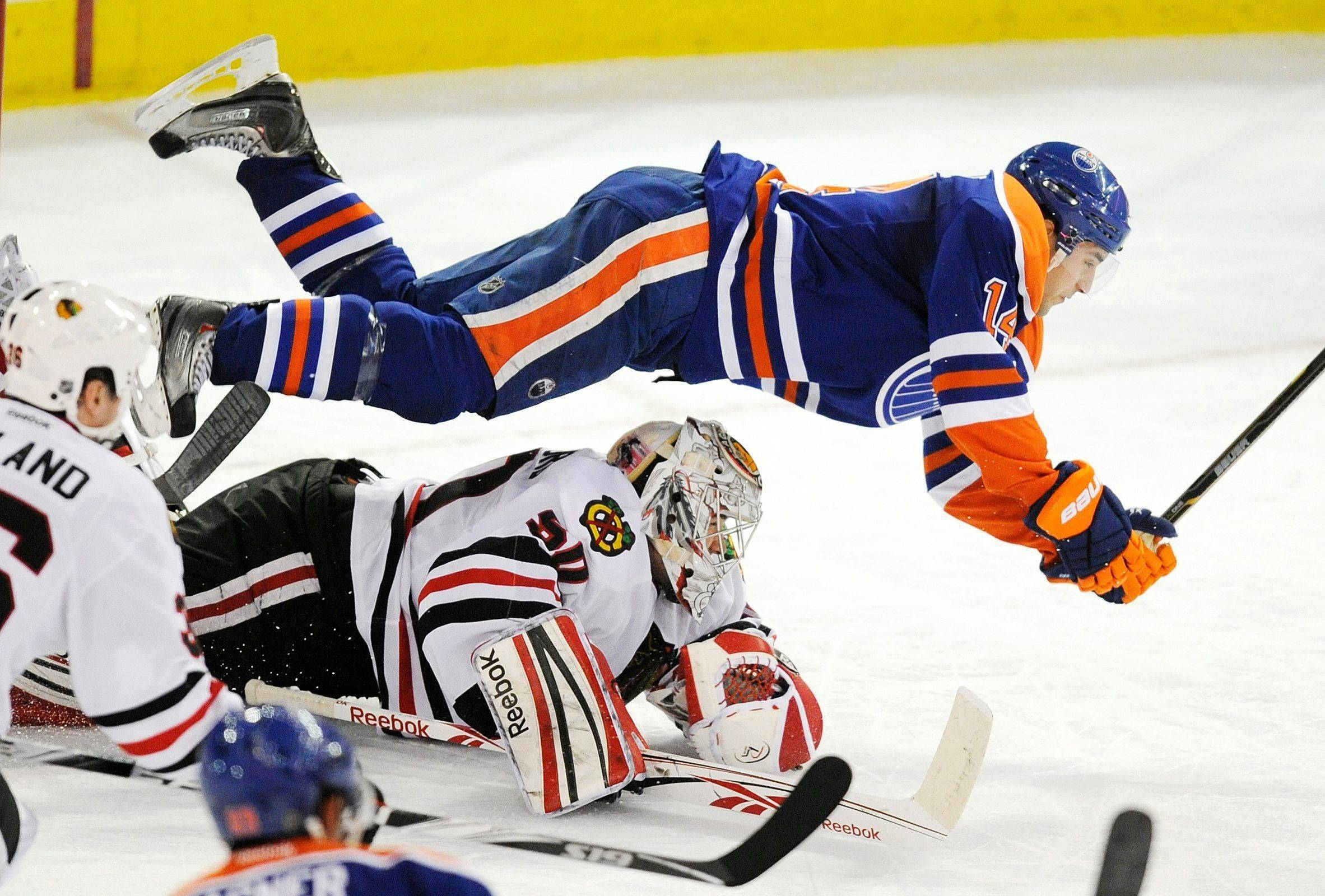 Edmonton Oilers' Jordan Eberle, top, flies over the Chicago Blackhawks goalie Cory Crawford during the second period of an NHL hockey game in Edmonton, Alberta, on Thursday, Feb. 2, 2012.