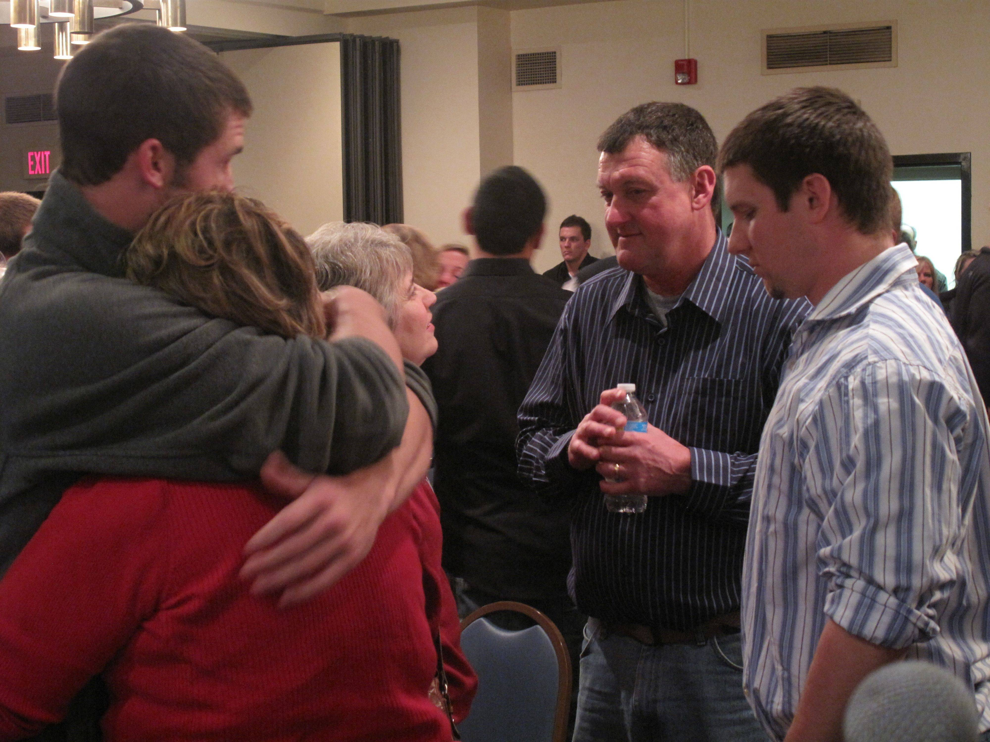 Shaun Wild's mom receives a hug while a woman talks to his dad after a community gathering Saturday night at North Central College.