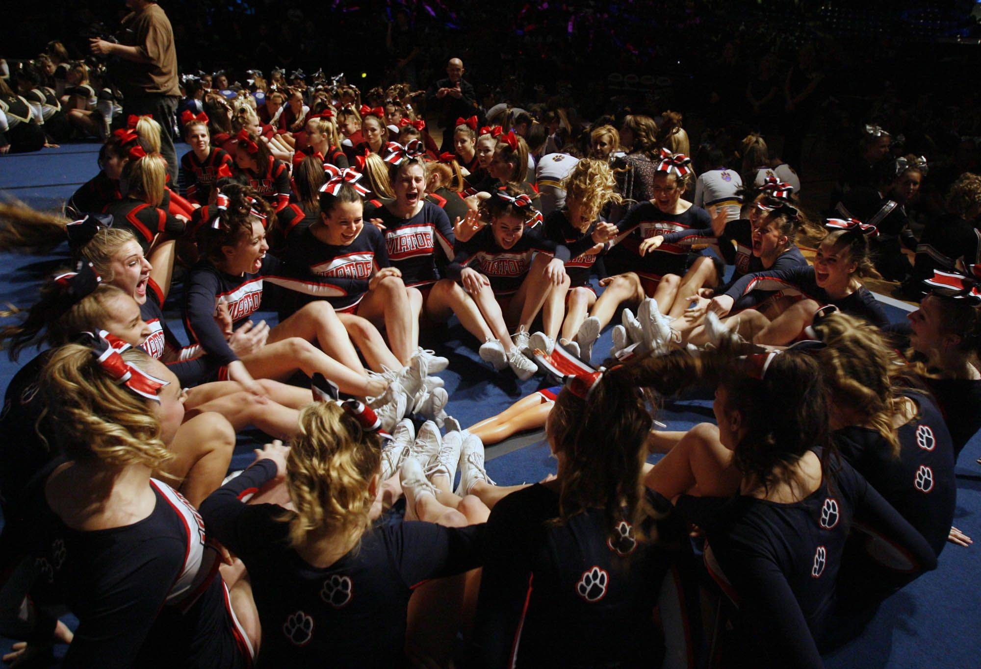 St. Viator High School cheerleading team members hear the announcement they took first place at state finals for the medium school category at U.S. Cellular Coliseum in Bloomington on Saturday.