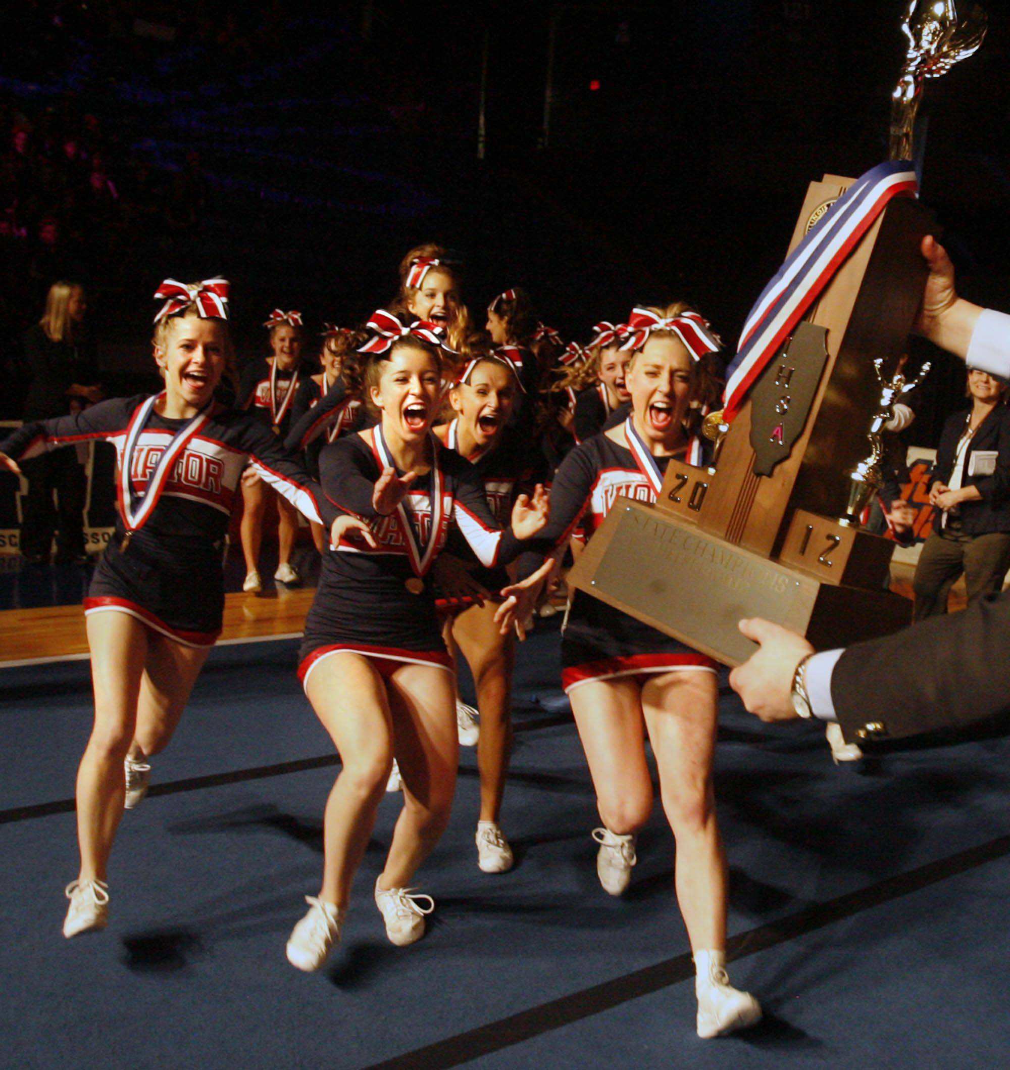 St. Viator High School cheerleading team raises to accept the first place trophy for the medium school category at IHSA cheerleading state finals at U.S. Cellular Coliseum in Bloomington on Saturday.