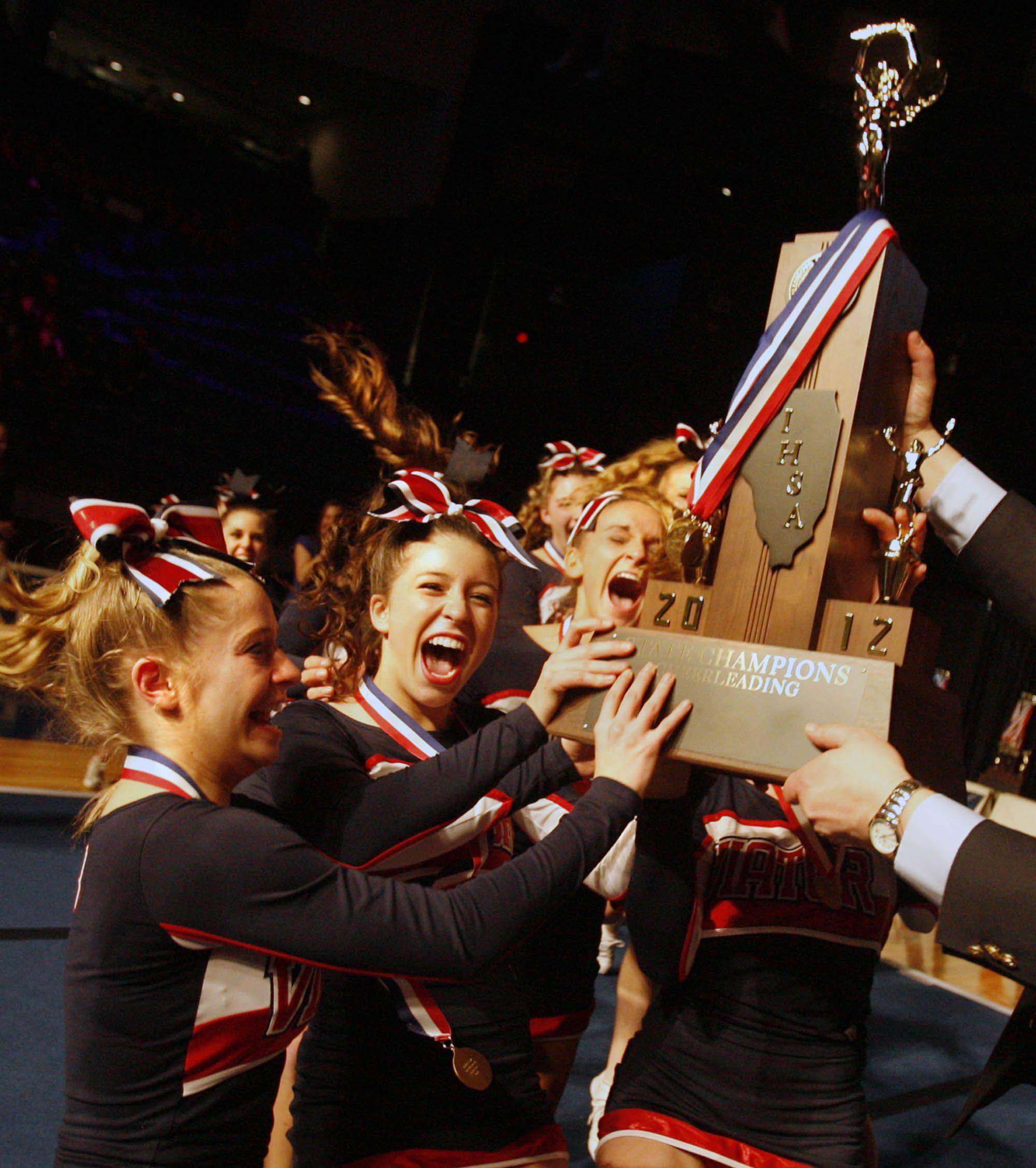 St. Viator high school cheerleading team raises to accept the first place trophy for the medium school category at IHSA cheerleading state finals at U.S. Cellular Coliseum in Bloomington on Saturday, February 4th.