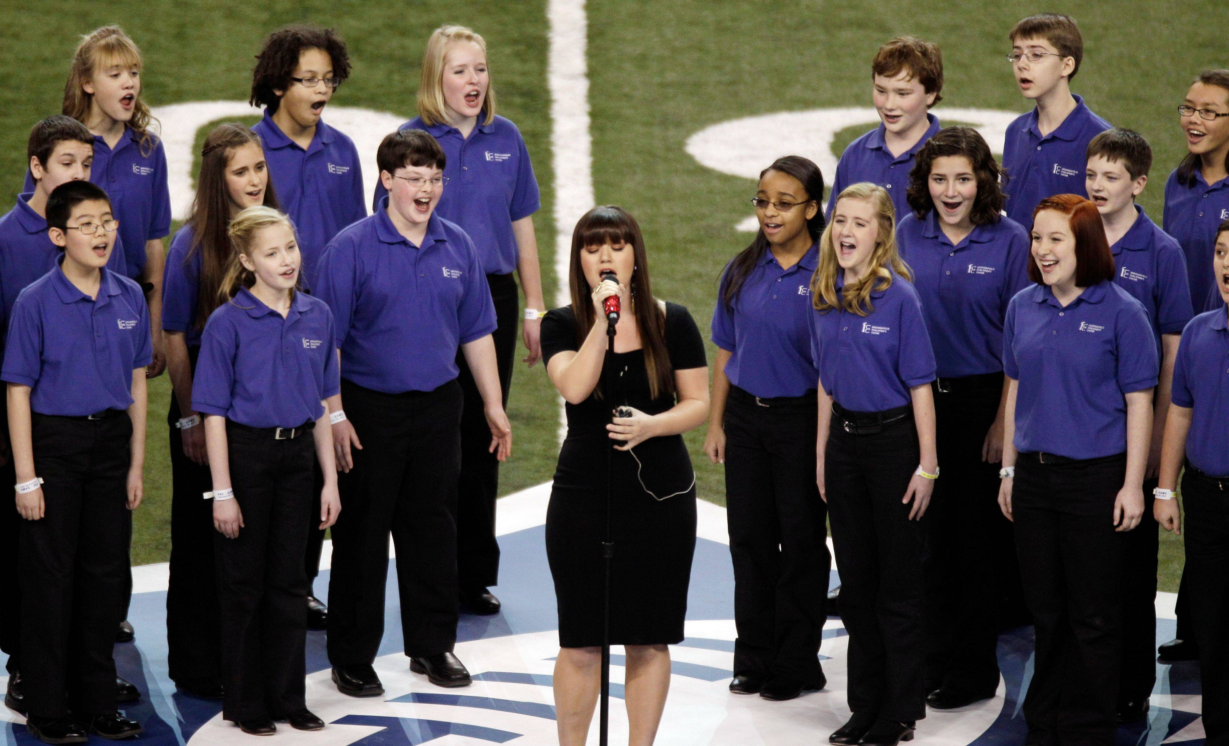 Kelly Clarkson performs the national anthem with the Indianapolis Children's Choir before the NFL Super Bowl XLVI football game between the New York Giants and the New England Patriots Sunday in Indianapolis.