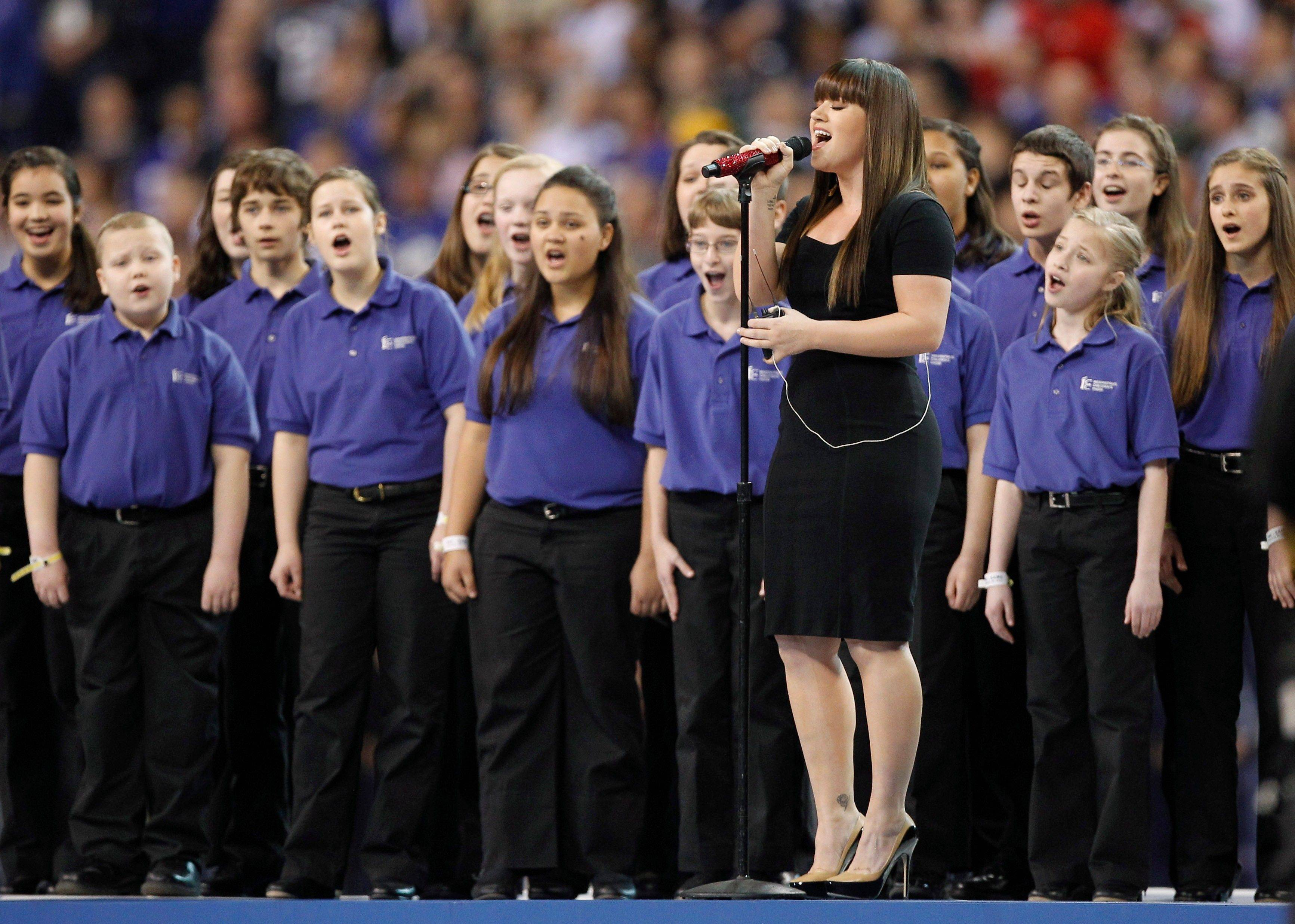 Kelly Clarkson sings the national anthem with the Indianapolis Children's Choir before the NFL Super Bowl XLVI football game between the New York Giants and the New England Patriots Sunday in Indianapolis.