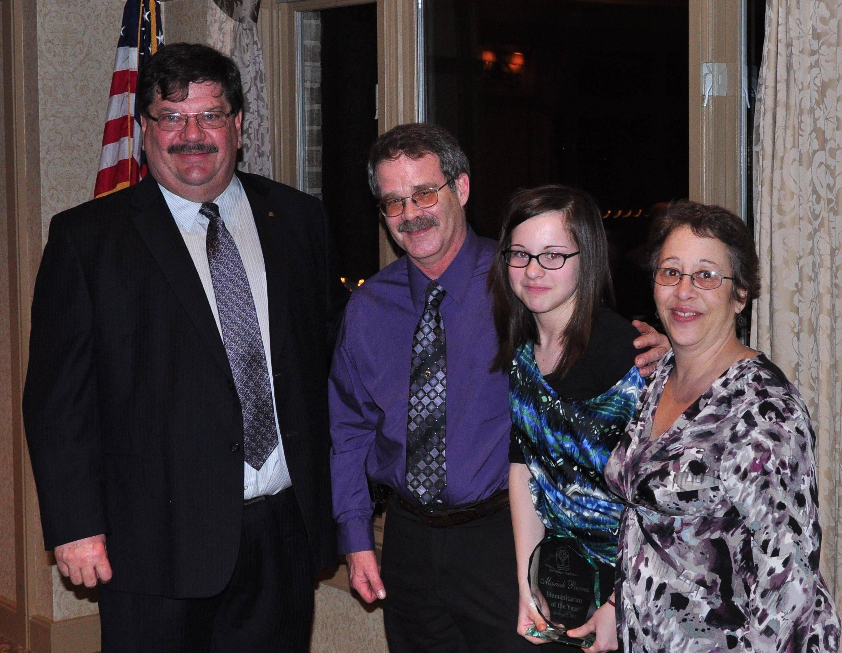 Hanover Park Mayor Rod Craig congratulates Mariah Reeves, 12, standing with her parents, for winning the village's Humanitarian of the Year award. Reeves earned the award by donating a portion of the gifts she received from her bat mitzvah to the family of a 3-year-old boy in need of a kidney transplant.