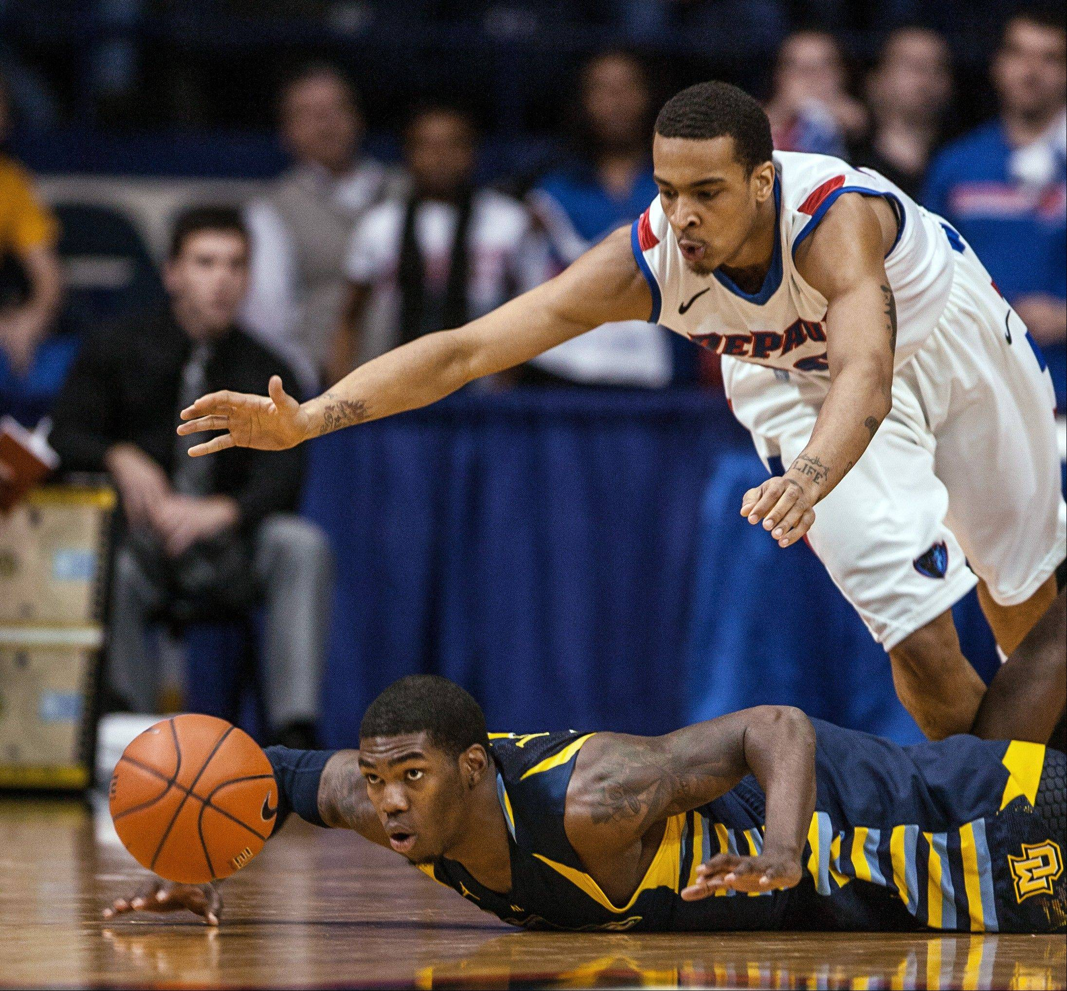 DePaul's Brandon Young dives over Marquette's Jamail Jones for the loose ball during the second half Monday night.