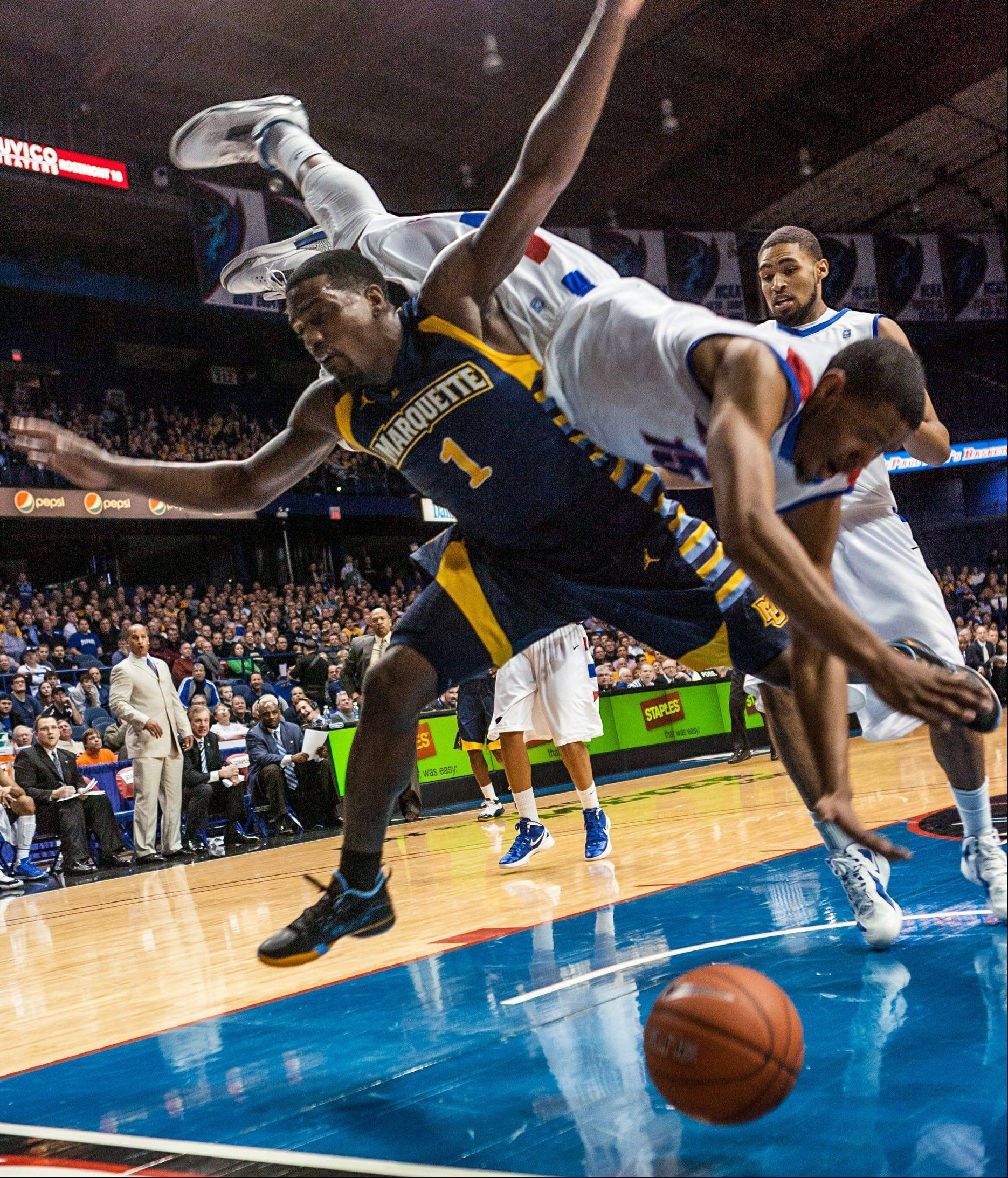 DePaul's Mose Morgan goes over the back of Marquette's Darius Johnson-Odom while trying to block his shot during the first half of an NCAA college basketball game Monday in Rosemont.