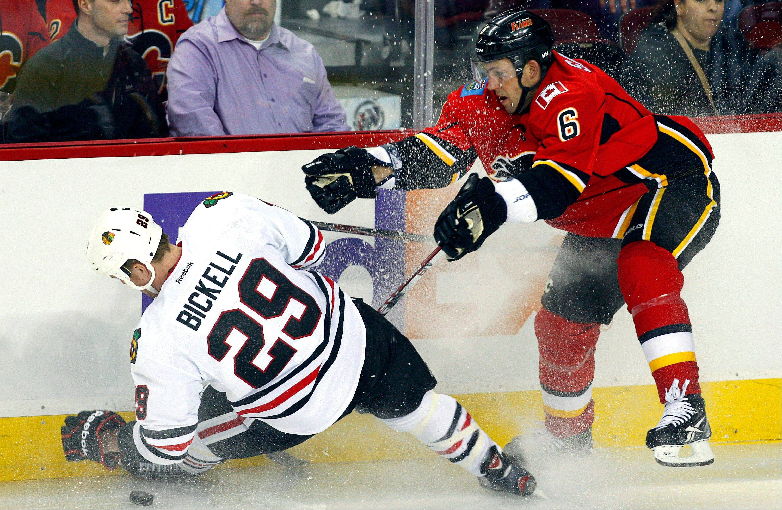 Bryan Bickell is sent to the ice by Calgary's Cory Sarich during the Hawks' loss to the Flames on Friday.