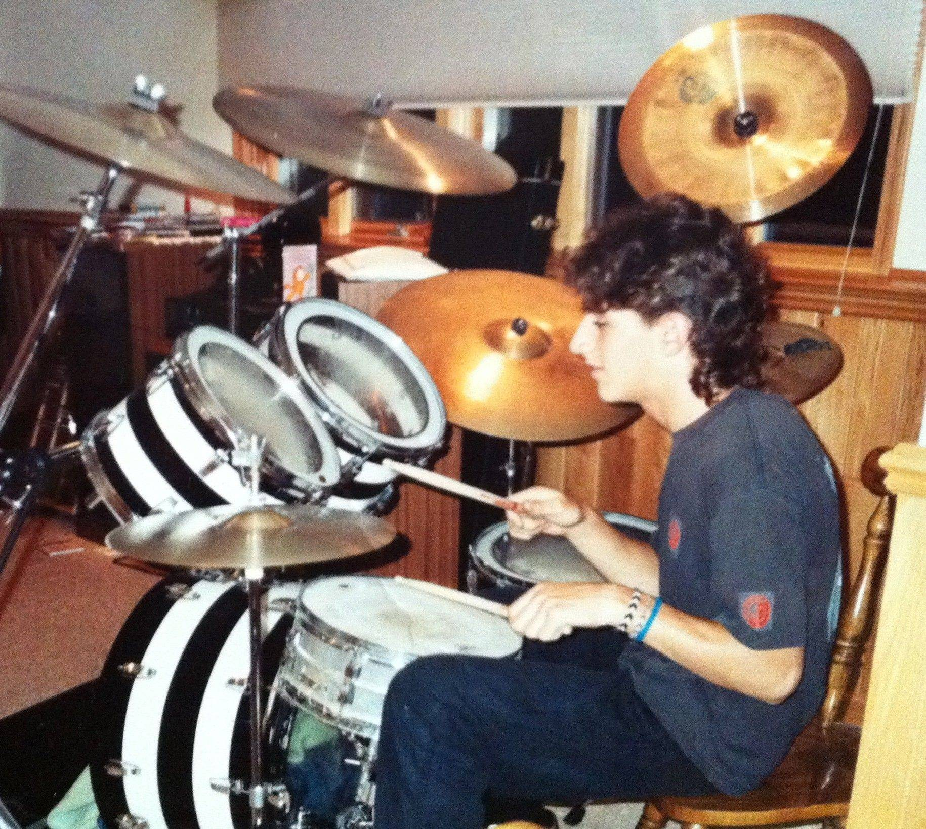 "OK GO drummer Dan Konopka, at age 14, sporting a ""glorious mullet"" and playing on his first drum set in the basement of his Elmhurst home. ""I had it set up in the basement -- I used a kitchen chair!"" he said. ""I wish I still had that kit. Stupidly, I traded it in for a way-less-cool-looking other set of drums."""