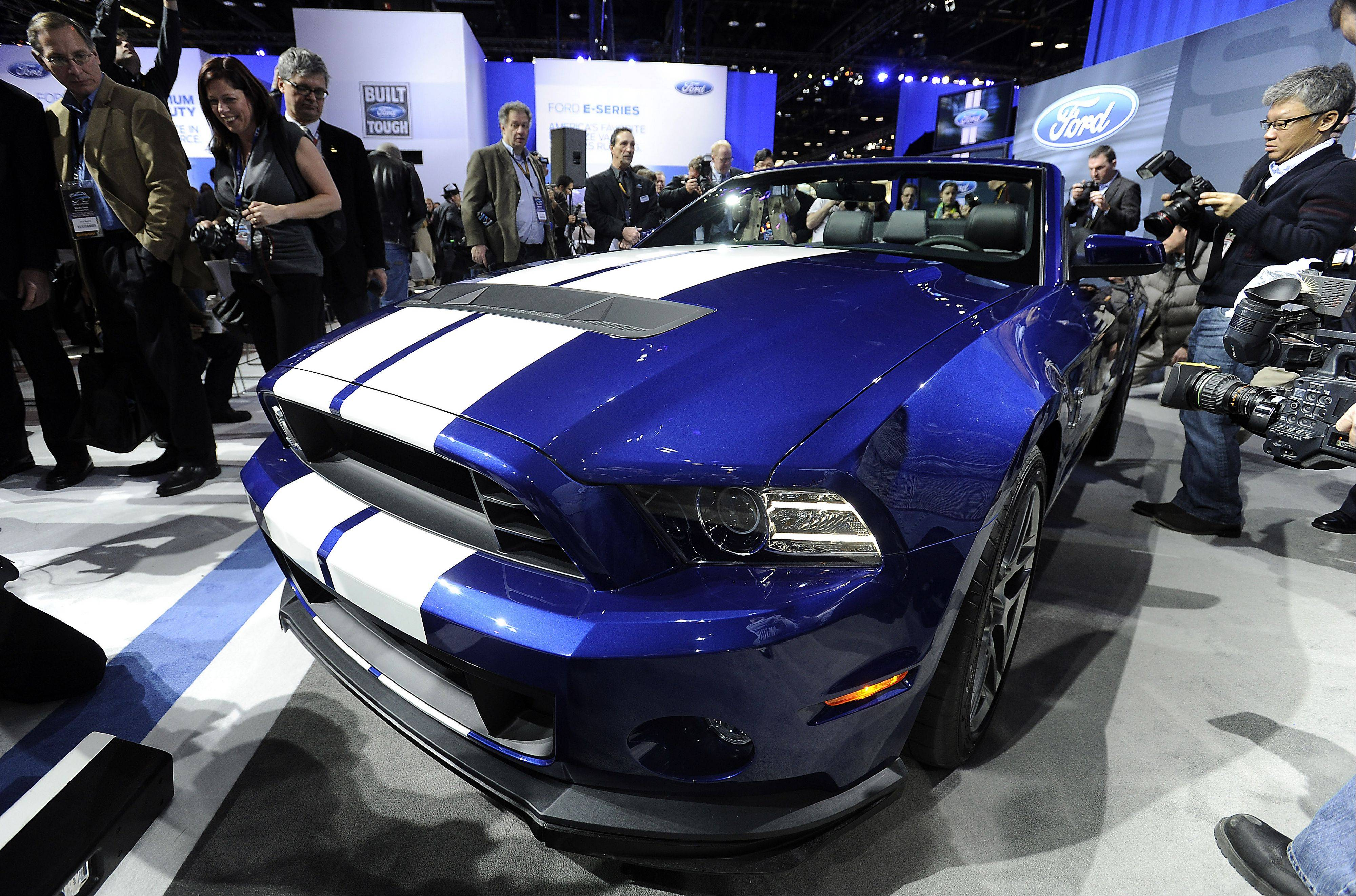 Photographers work and cameramen roll tape on the Ford GT 500 Shelby Mustang, featuring a 600-horsepower V8.